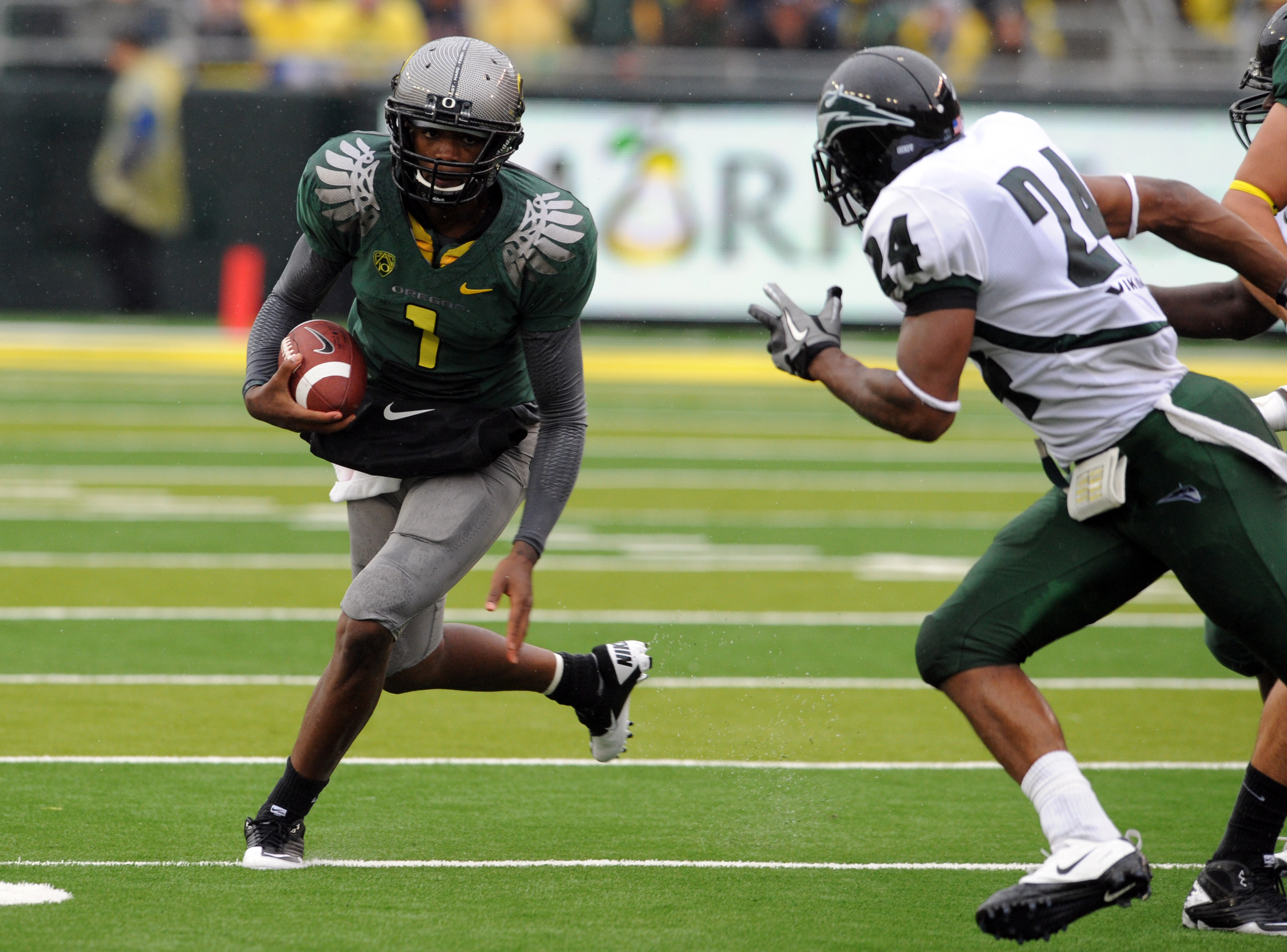 EUGENE, OR - SEPTEMBER 18: Quarterback Darron Thomas #1 of the Oregon Ducks looks for some running room as cornerback Deshawn Shead #24 of the Portland State Vikings closes in during the first quarter of the game against  at Autzen Stadium on September 18