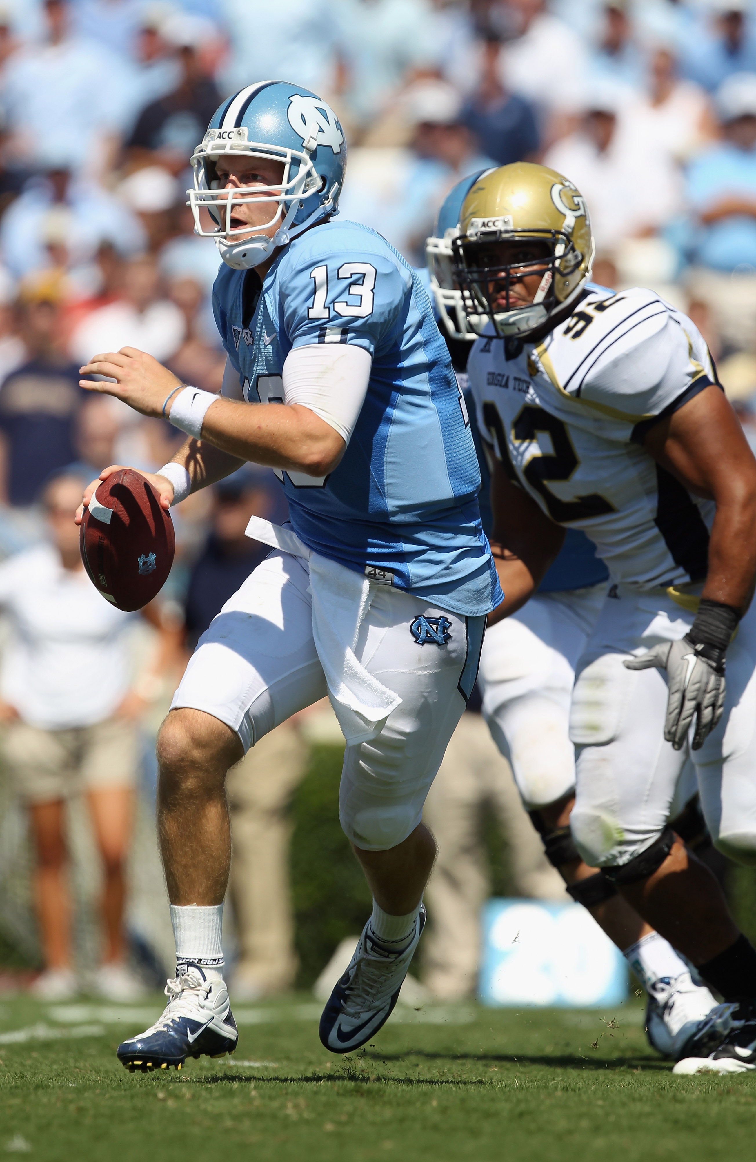 CHAPEL HILL, NC - SEPTEMBER 18:  T.J. Yates #13 of the North Carolina Tar Heels runs away from Jason Peters #92 of the Georgia Tech Yellow Jackets during their game at Kenan Stadium on September 18, 2010 in Chapel Hill, North Carolina.  (Photo by Streeter
