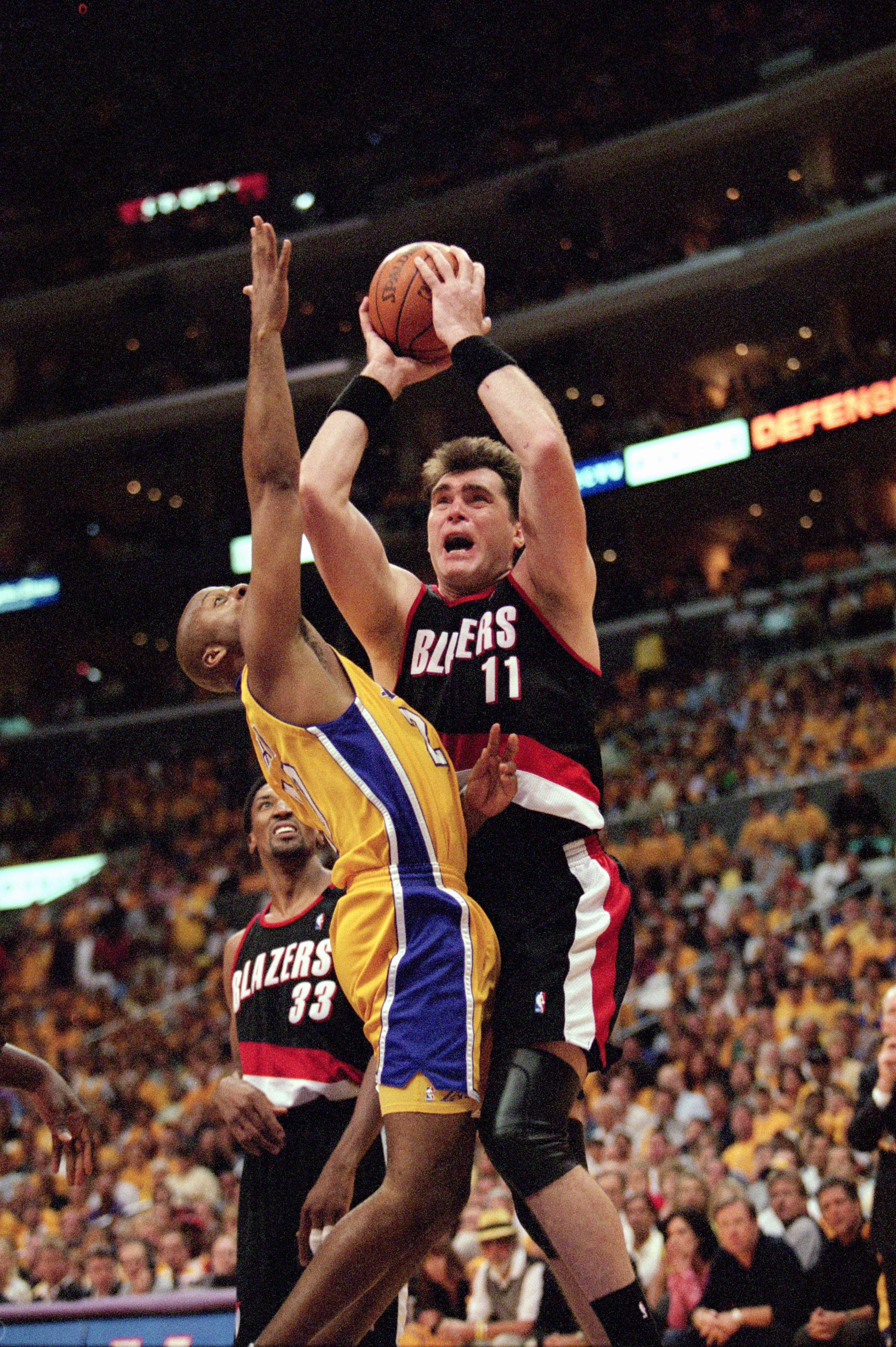 LOS ANGELES - JUNE 4:  Center Arvydas Sabonis #11 of the Portland Trail Blazers puts up a shot pressured by Brian Shaw #20 of the Los Angeles Lakers during Game 7 of the Western Conference Finals at Staples Center on June 4, 2000 in Los Angeles, Californi