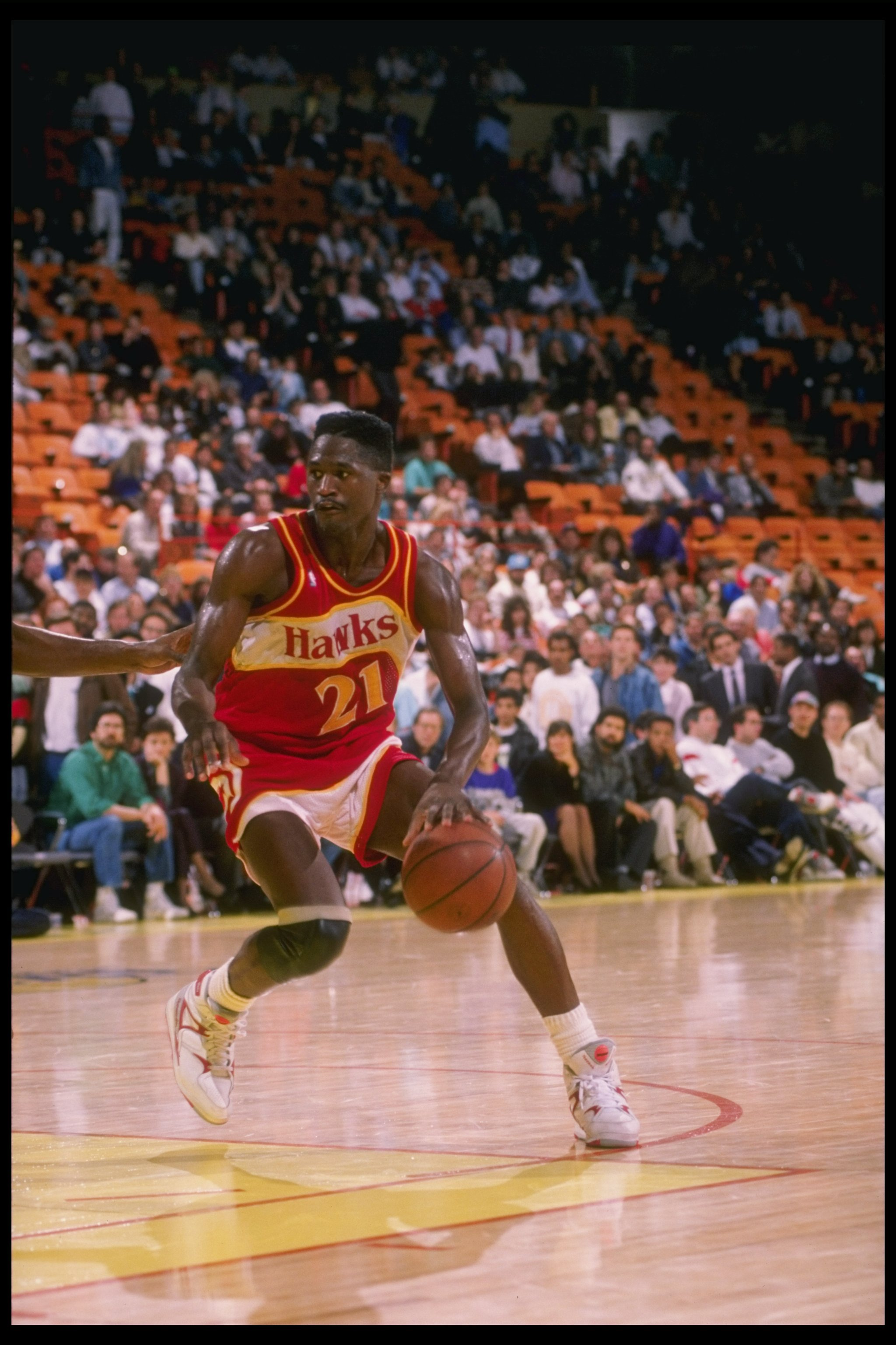 Forward Dominique Wilkins of the Atlanta Hawks dribbles down the court during a game.