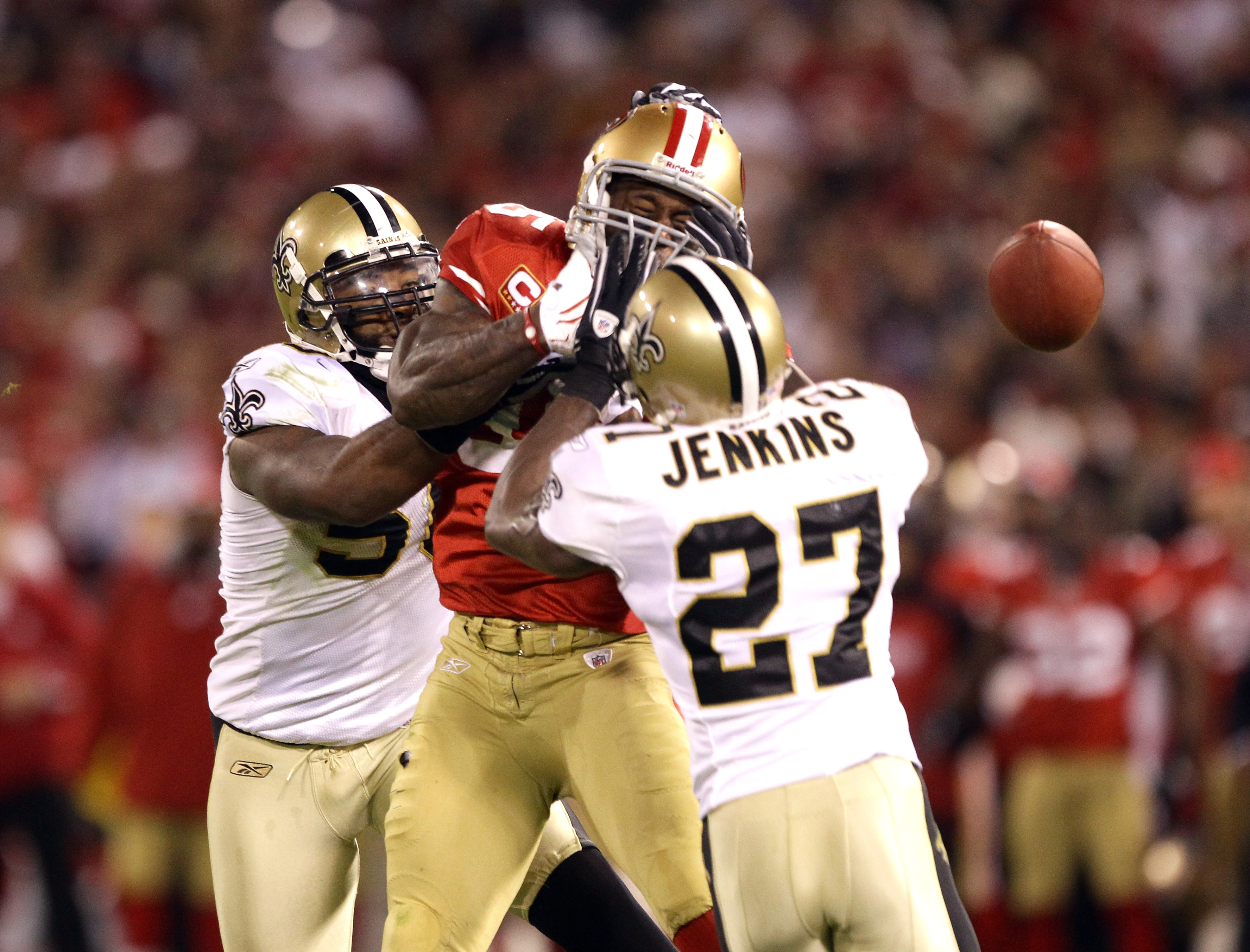 SAN FRANCISCO - SEPTEMBER 20:  Vernon Davis #85 of the San Francisco 49ers loses the ball while defended by Malcolm Jenkins #27 and Marvin Mitchell #50 of the New Orleans Saints at Candlestick Park on September 20, 2010 in San Francisco, California.  (Pho