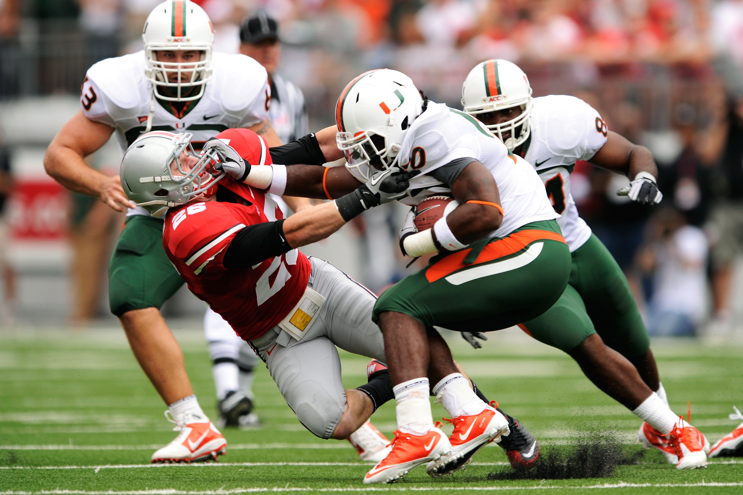 COLUMBUS, OH - SEPTEMBER 11:  Damien Berry #20 of the Miami Hurricanes stiff arms Tyler Moeller #26 of the Ohio State Buckeyes as Moeller attempts to tackle Berry at Ohio Stadium on September 11, 2010 in Columbus, Ohio.  (Photo by Jamie Sabau/Getty Images