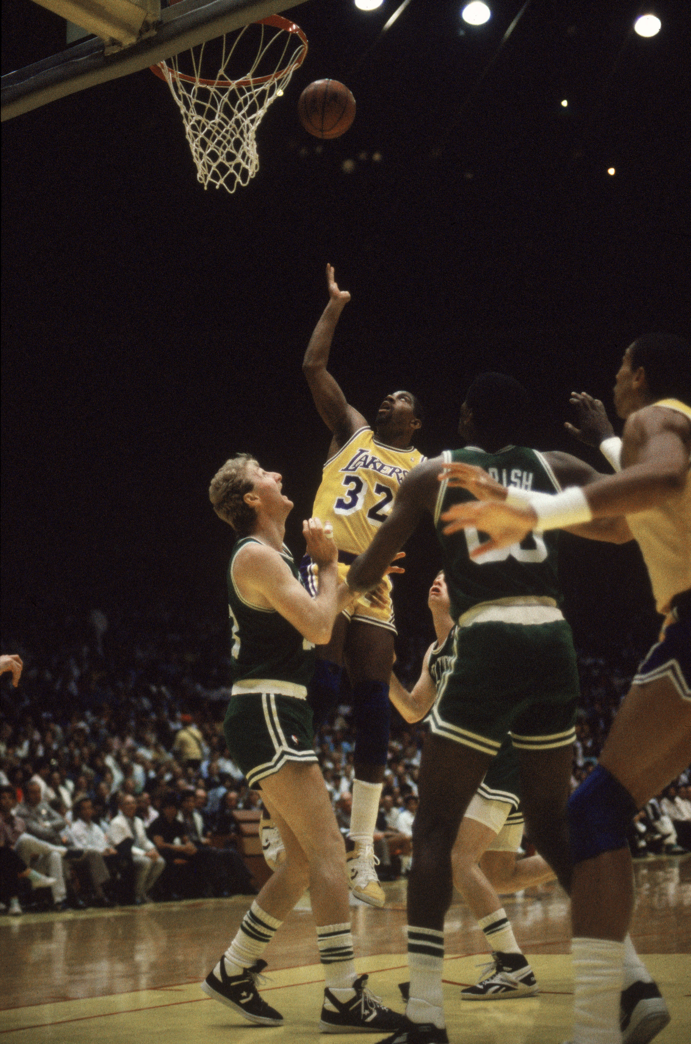 LOS ANGELES - 1987:  Magic Johnson #32 of the Los Angeles Lakers rebounds over Larry Bird #33 of the Boston Celtics during an NBA Finals game at the Great Western Forum in Los Angeles, California in 1987. (Photo by: Mike Powell/Getty Images)
