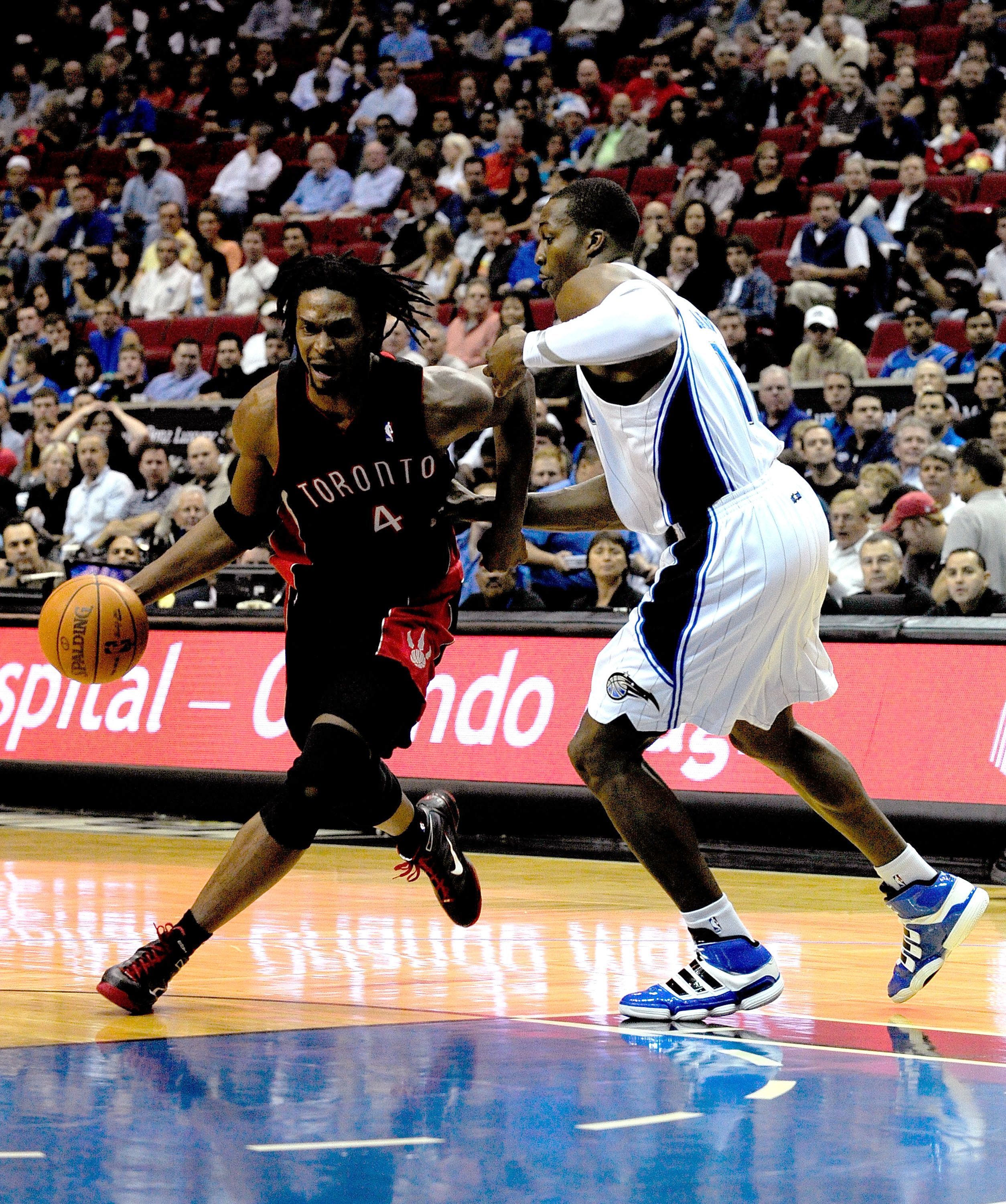ORLANDO, FL - DECEMBER 16:  Chris Bosh #4 of the Toronto Raptors attempts to drives past Dwight Howard #12 of the Orlando Magic during the game at Amway Arena on December 16, 2009 in Orlando, Florida.  NOTE TO USER: User expressly acknowledges and agrees
