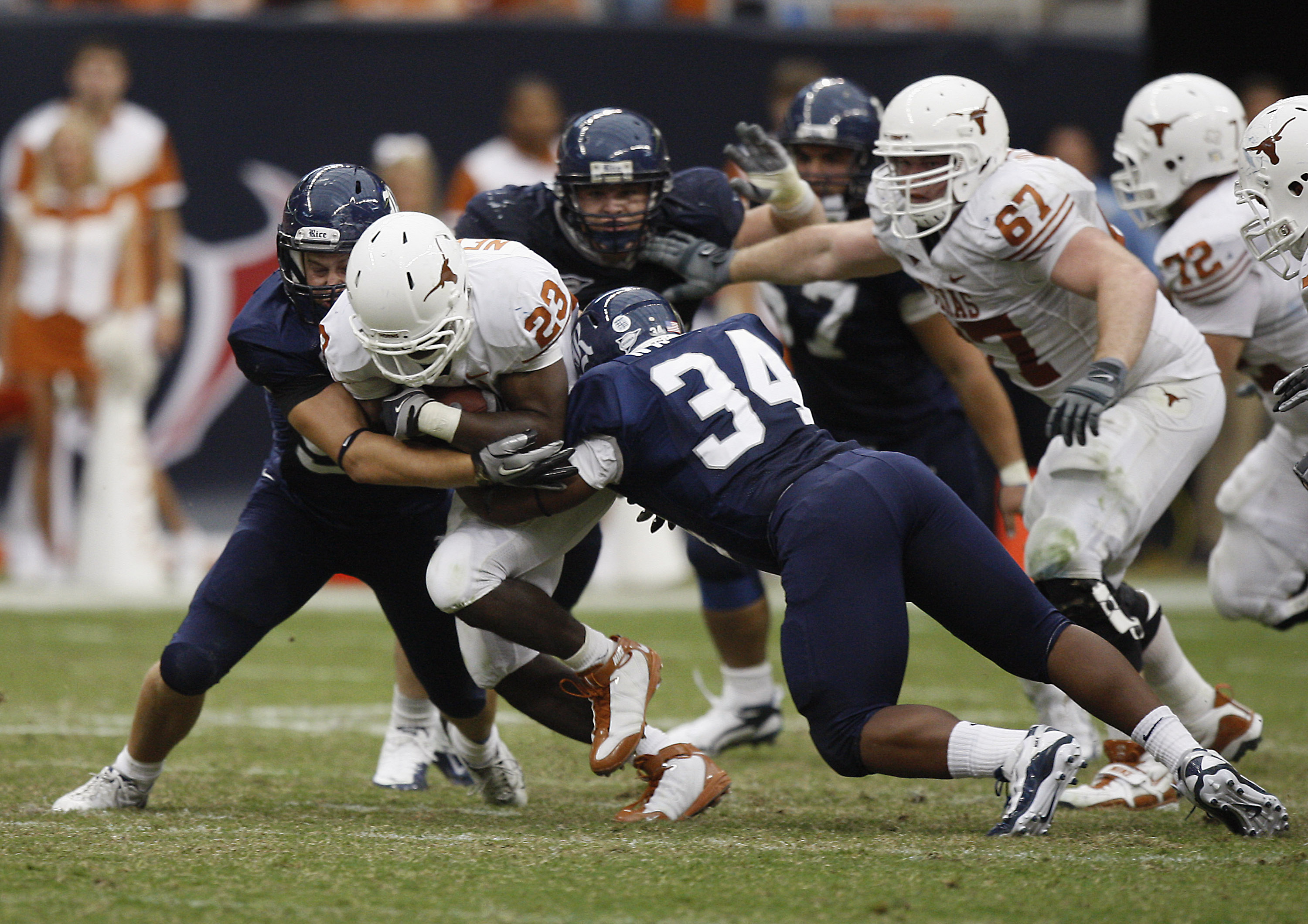HOUSTON - SEPTEMBER 04:  Running back Tre' Newton #23 of the Texas Longhorns is tackled by linebacker Cameron Nwosu #34 of the Rice Owls at Reliant Stadium on September 4, 2010 in Houston, Texas.  (Photo by Bob Levey/Getty Images)