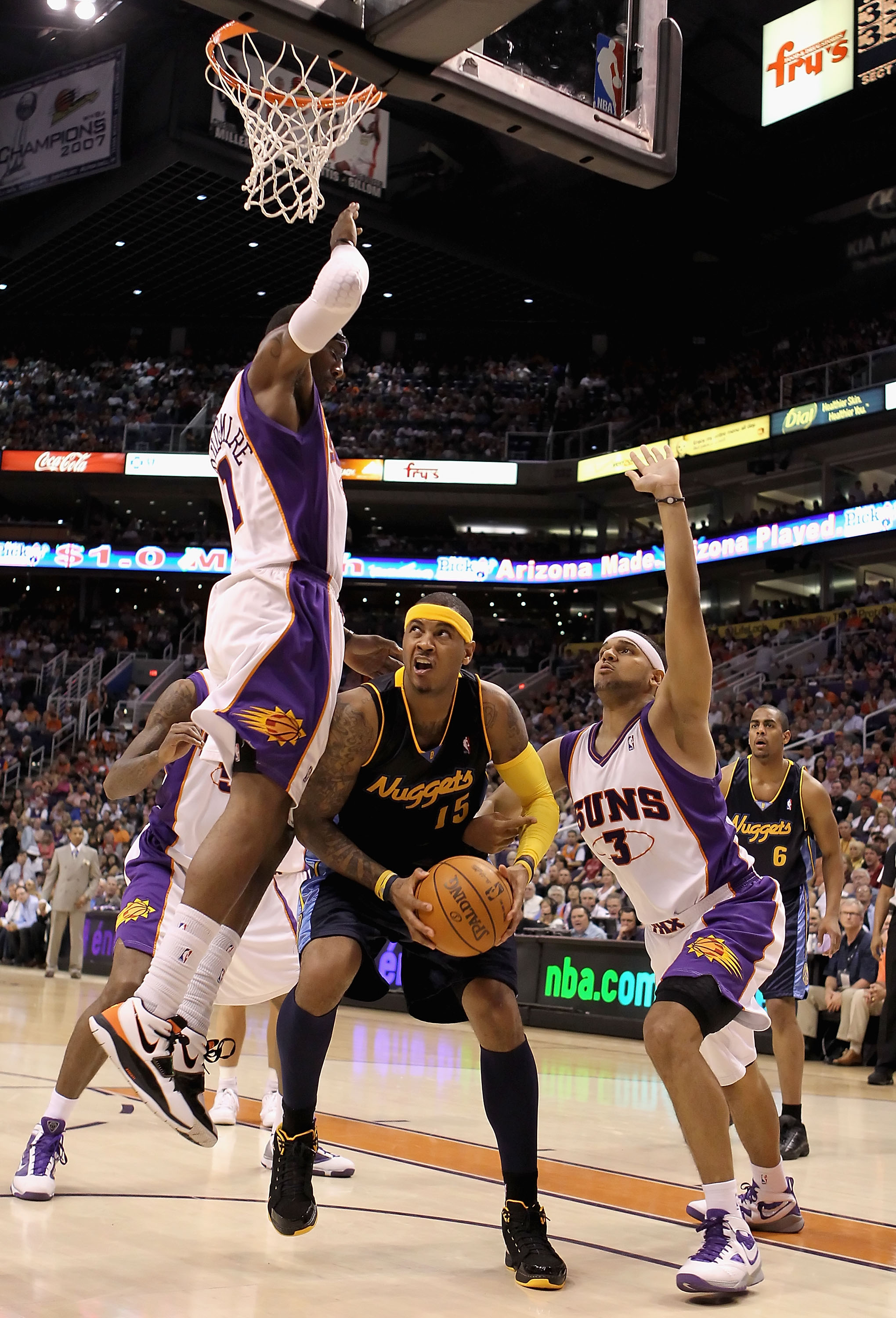 PHOENIX - APRIL 13:  Carmelo Anthony #15 of the Denver Nuggets handles the ball under pressure from Amar'e Stoudemire #1 and Jared Dudley #3 of the Phoenix Suns during the NBA game at US Airways Center on April 13, 2010 in Phoenix, Arizona. NOTE TO USER: