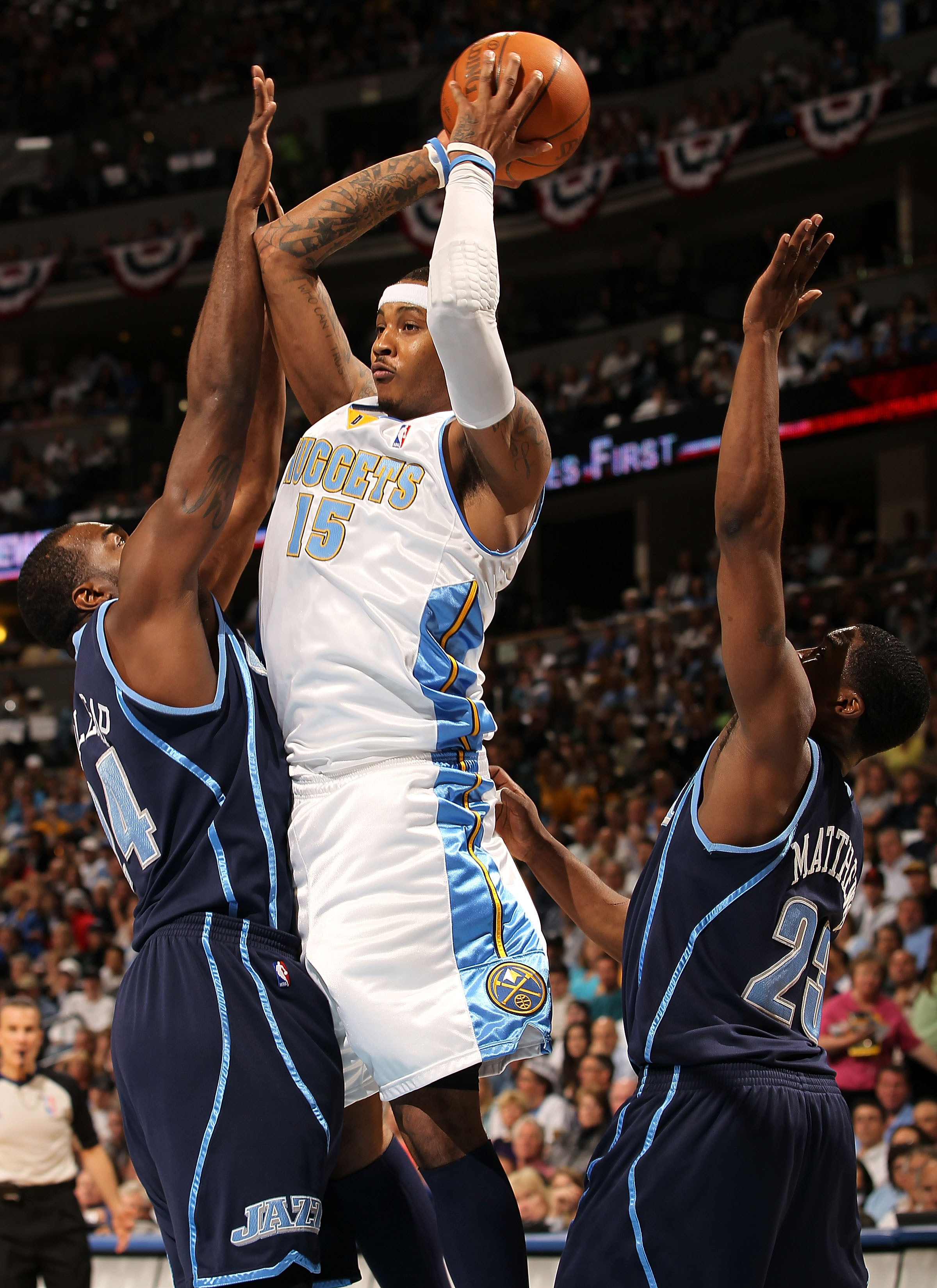 DENVER - APRIL 19:  Carmelo Anthony #15 of the Denver Nuggets looks to make a pass between the defense of Paul Millsap #24 and Wesley Mathews #23 of the Utah Jazz in Game Two of the NBA Western Conference Quarterfinals at the Pepsi Center on April 19, 201