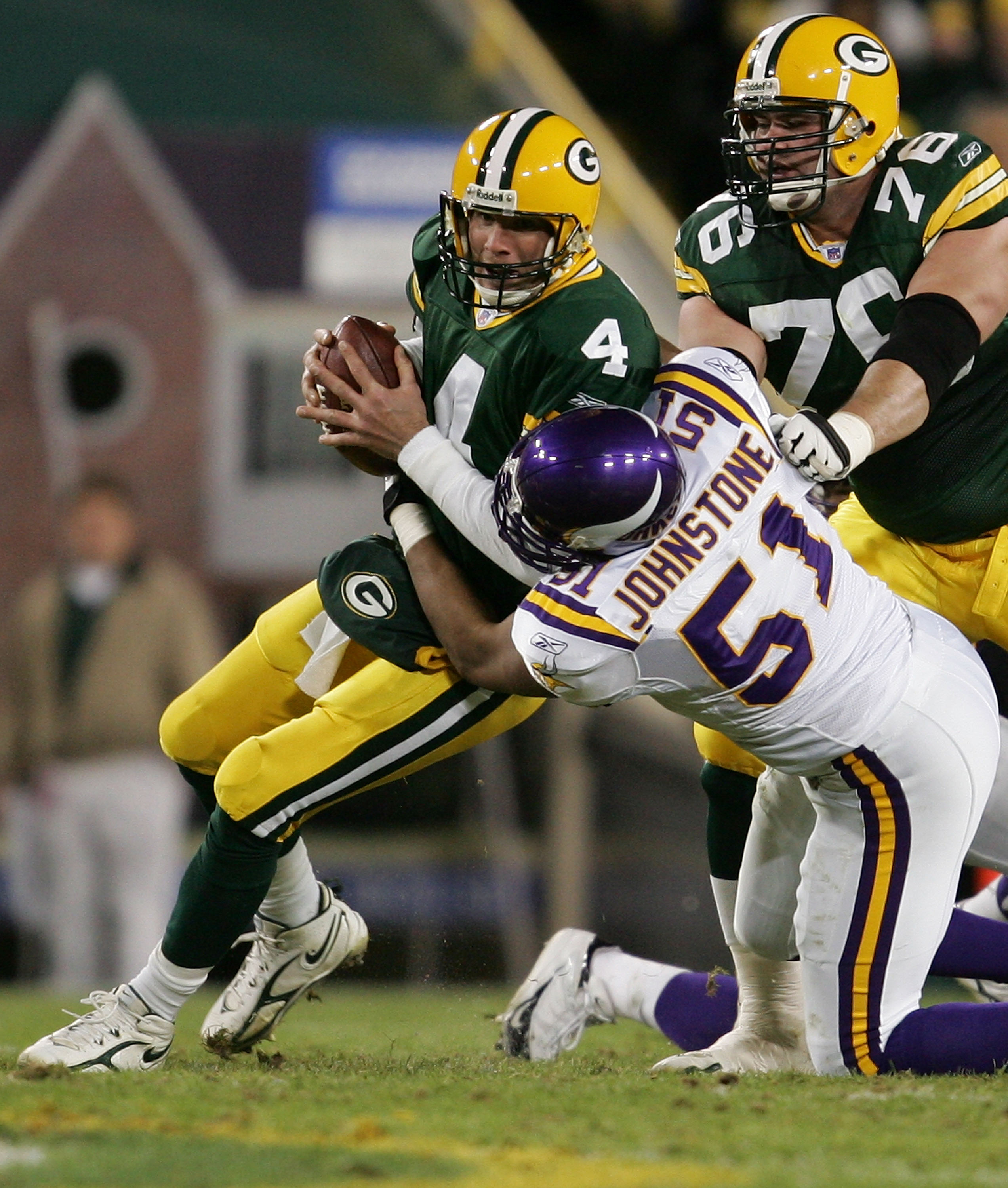 GREEN BAY, WI - NOVEMBER 21:  Quarterback Brett Favre #4 of the Green Bay Packers is sacked by Lance Johnstone #51 of the Minnesota Vikings as Chad Clifton #76 tries to block in NHL action November 21, 2005 at Lambeau Field in Green Bay, Wisconsin.  (Phot