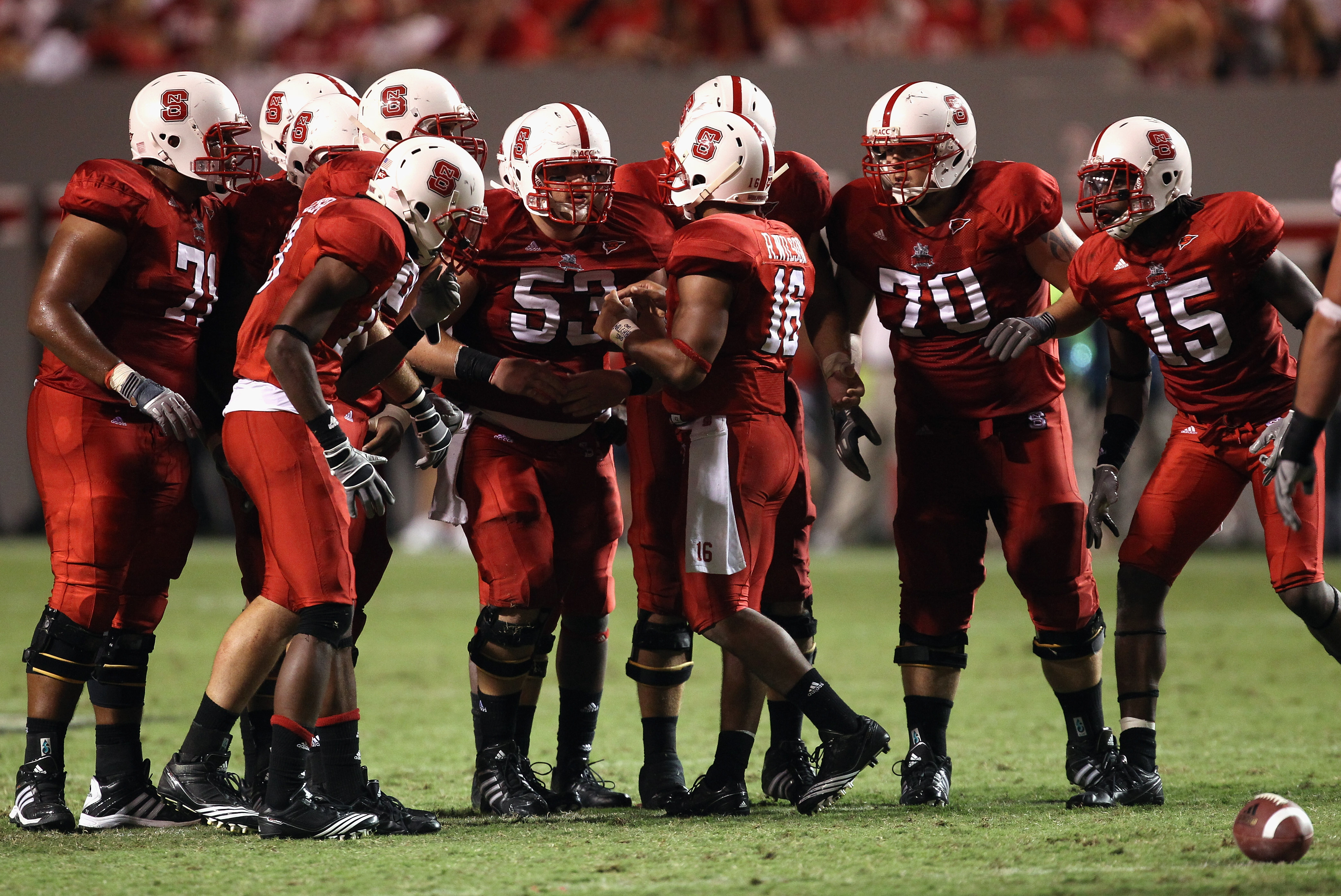 RALEIGH, NC - SEPTEMBER 16:  Russell Wilson #16 of the North Carolina State Wolfpack talks to his team in the huddle against the Cincinnati Bearcats during their game at Carter-Finley Stadium on September 16, 2010 in Raleigh, North Carolina.  (Photo by St