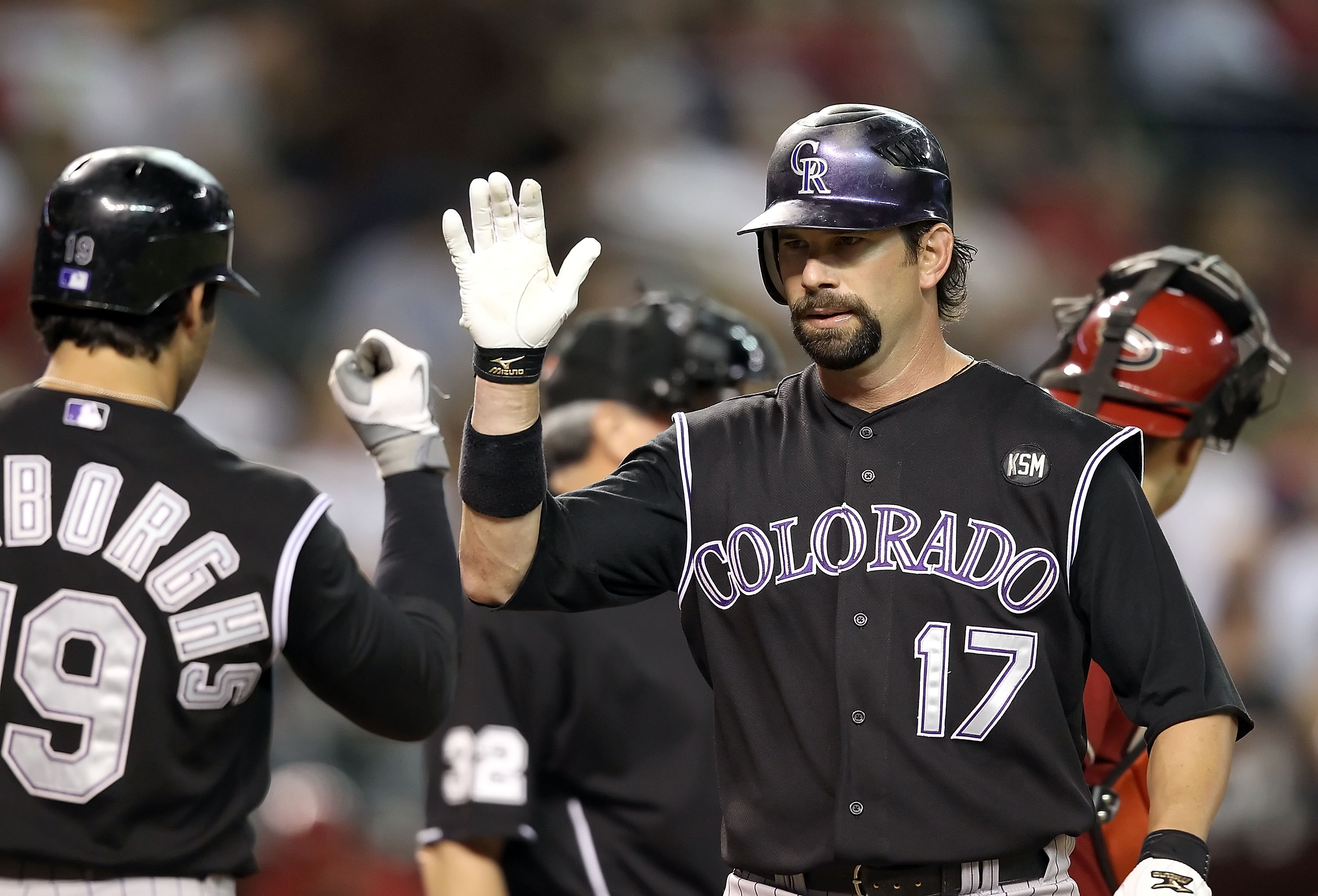 PHOENIX - SEPTEMBER 22:  Todd Helton #17 of the Colorado Rockies high fives teammate Ryan Spilborghs #16 after Helton hit a solo home run against the Arizona Diamondbacks during the first inning of the Major League Baseball game at Chase Field on Septembe