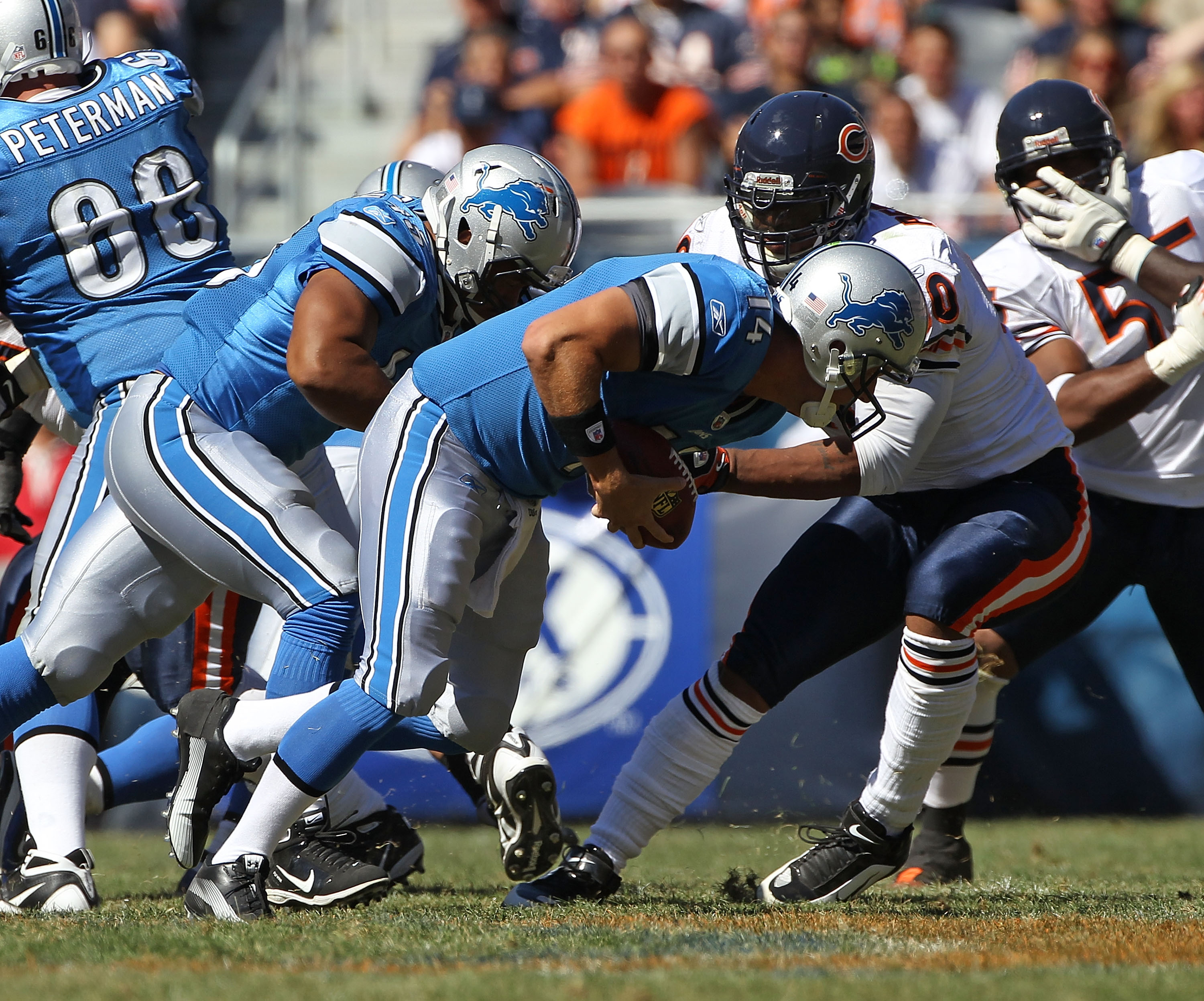 CHICAGO - SEPTEMBER 12: Shaun Hill #14 of the Detroit Lions tries to run after recovering his own fumbled snap as Julius Peppers #90 of the Chicago Bears attempts the tackle during the NFL season opening game at Soldier Field on September 12, 2010 in Chic