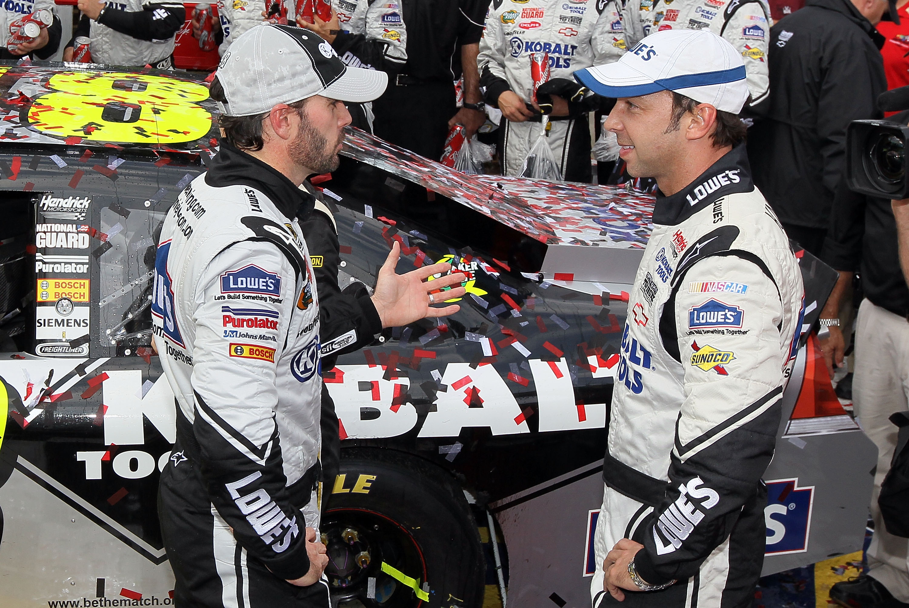 DOVER, DE - SEPTEMBER 26:  Jimmie Johnson (L), driver of the #48 Lowe's Chevrolet, and crew chief Chad Knaus talk in Victory Lane after winning the NASCAR Sprint Cup Series AAA 400 at Dover International Speedway on September 26, 2010 in Dover, Delaware.
