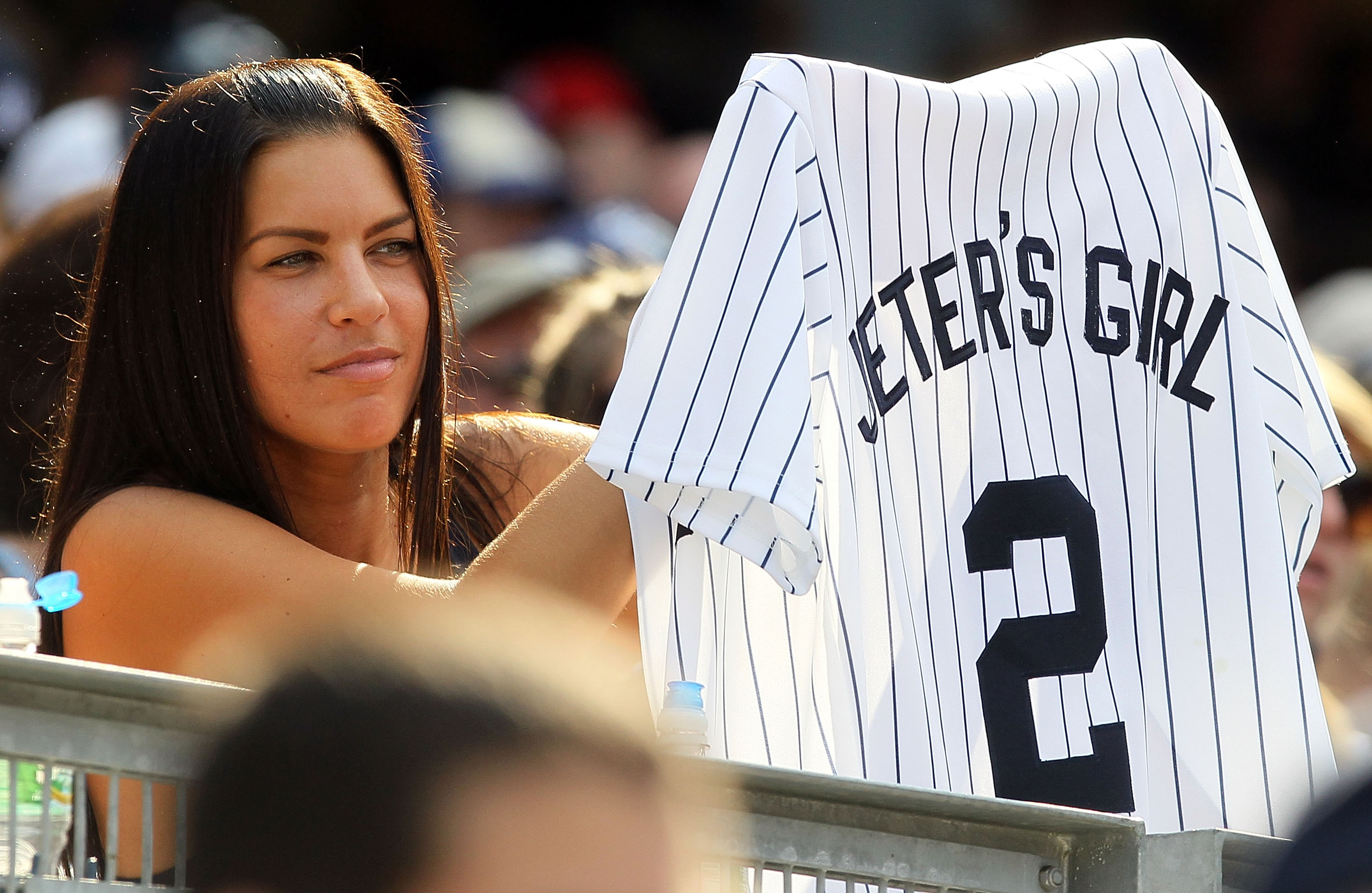 NEW YORK - JULY 18:  A fan of Derek Jeter of the New York Yankees holds up a jersey during the game against the Tampa Bay Rays on July 18, 2010 at Yankee Stadium in the Bronx borough of New York City. The Yankees defeated the Rays 9-5.  (Photo by Jim McIs