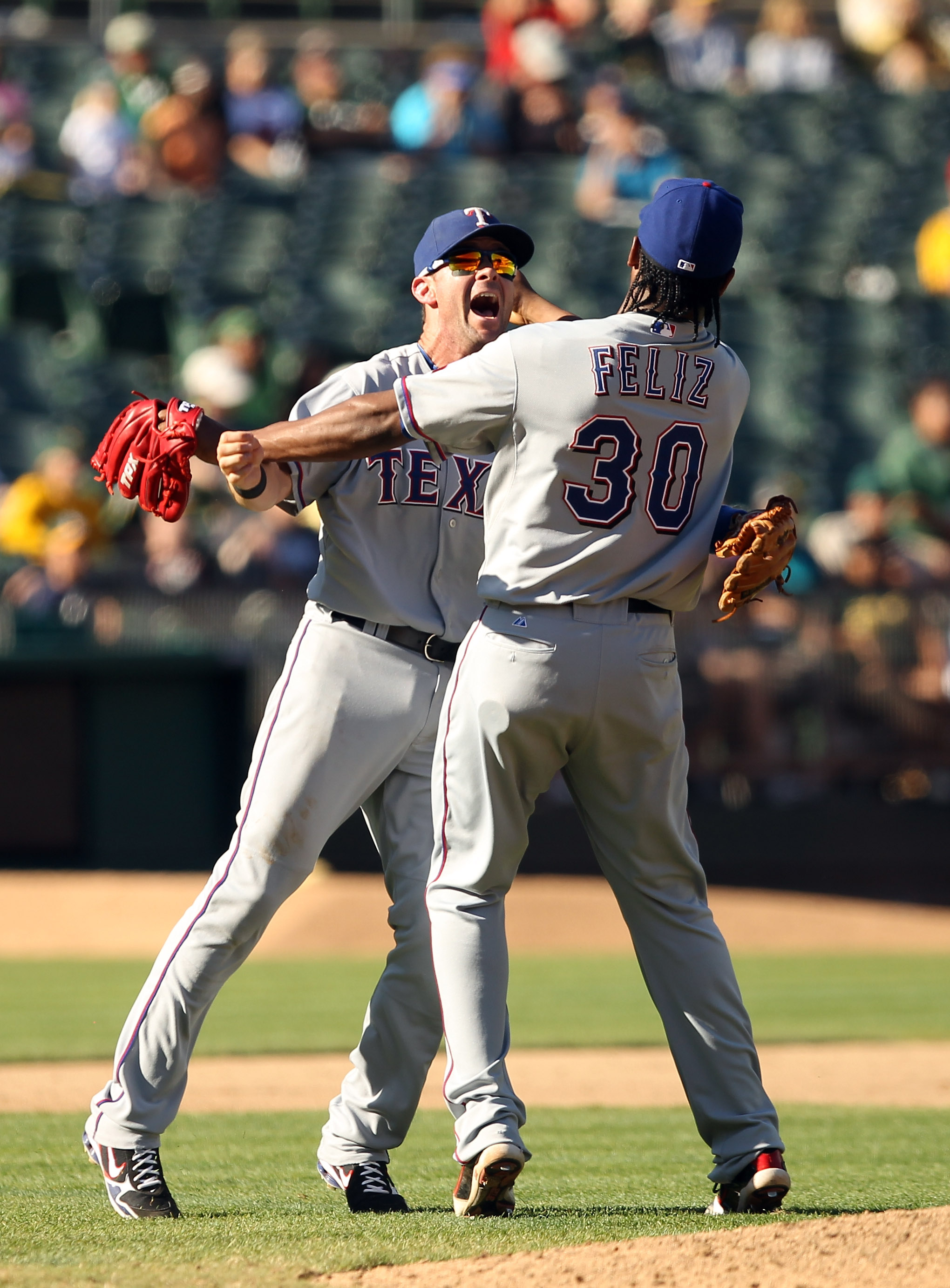 OAKLAND, CA - SEPTEMBER 25:  Michael Young #10 and Neftali Feliz #30 of the Texas Rangers celebrate after they beat the Oakland Athletics to clinch the American League West Title at the Oakland-Alameda County Coliseum on September 25, 2010 in Oakland, Cal