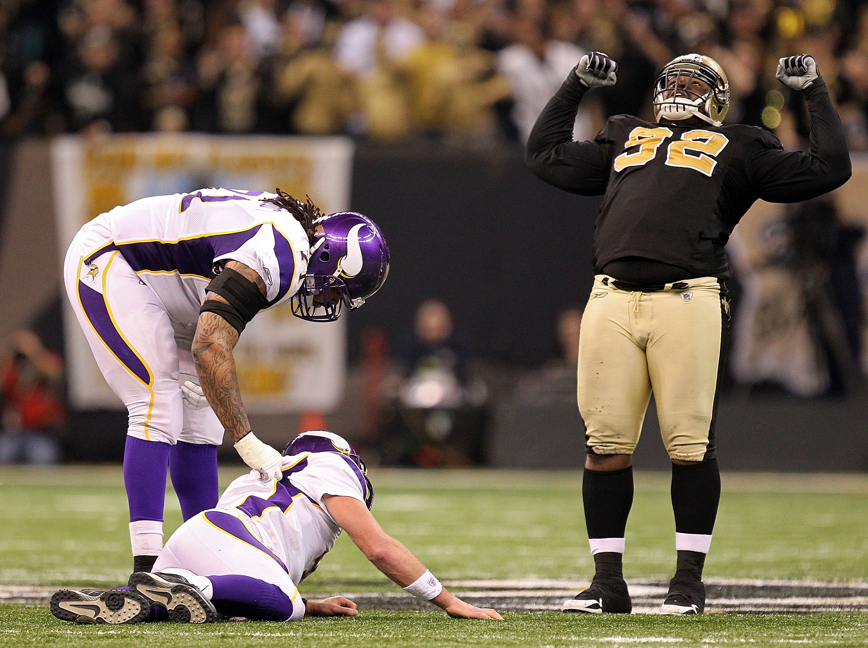 NEW ORLEANS - JANUARY 24:  Phil Loadholt #71 of the Minnesota Vikings checks on teammate Brett Favre #4  after he was hit by Remi Ayodele #92 of the New Orleans Saints during the NFC Championship Game at the Louisiana Superdome on January 24, 2010 in New