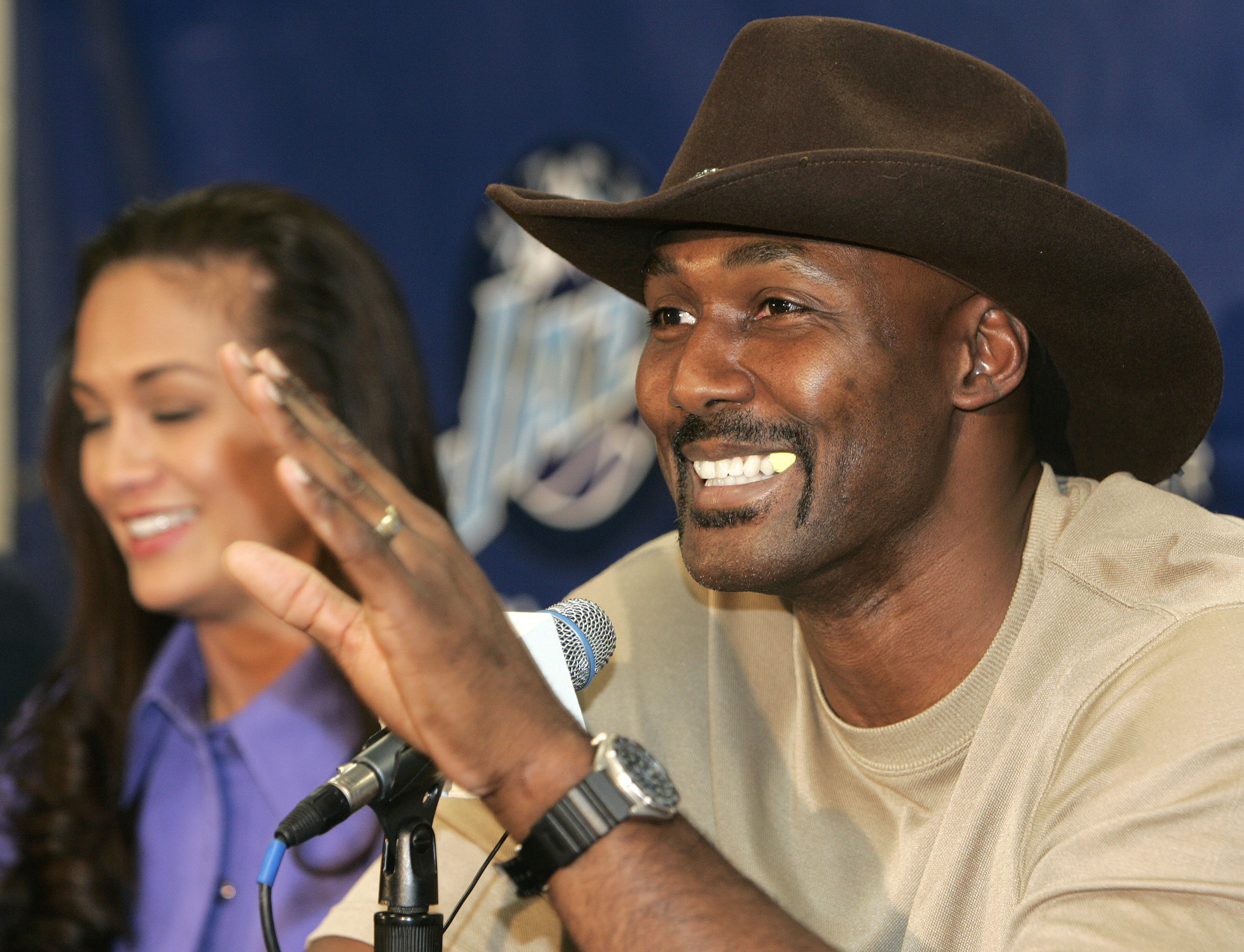 SALT LAKE CITY - FEBRUARY 13:  Karl Malone gestures as he announces his retirement from playing NBA basketball as his wife Kay (L) listens on February 13, 2005 at the Delta Center in Salt Lake City, Utah. Malone played 19 years in the NBA, 18 with the Uta