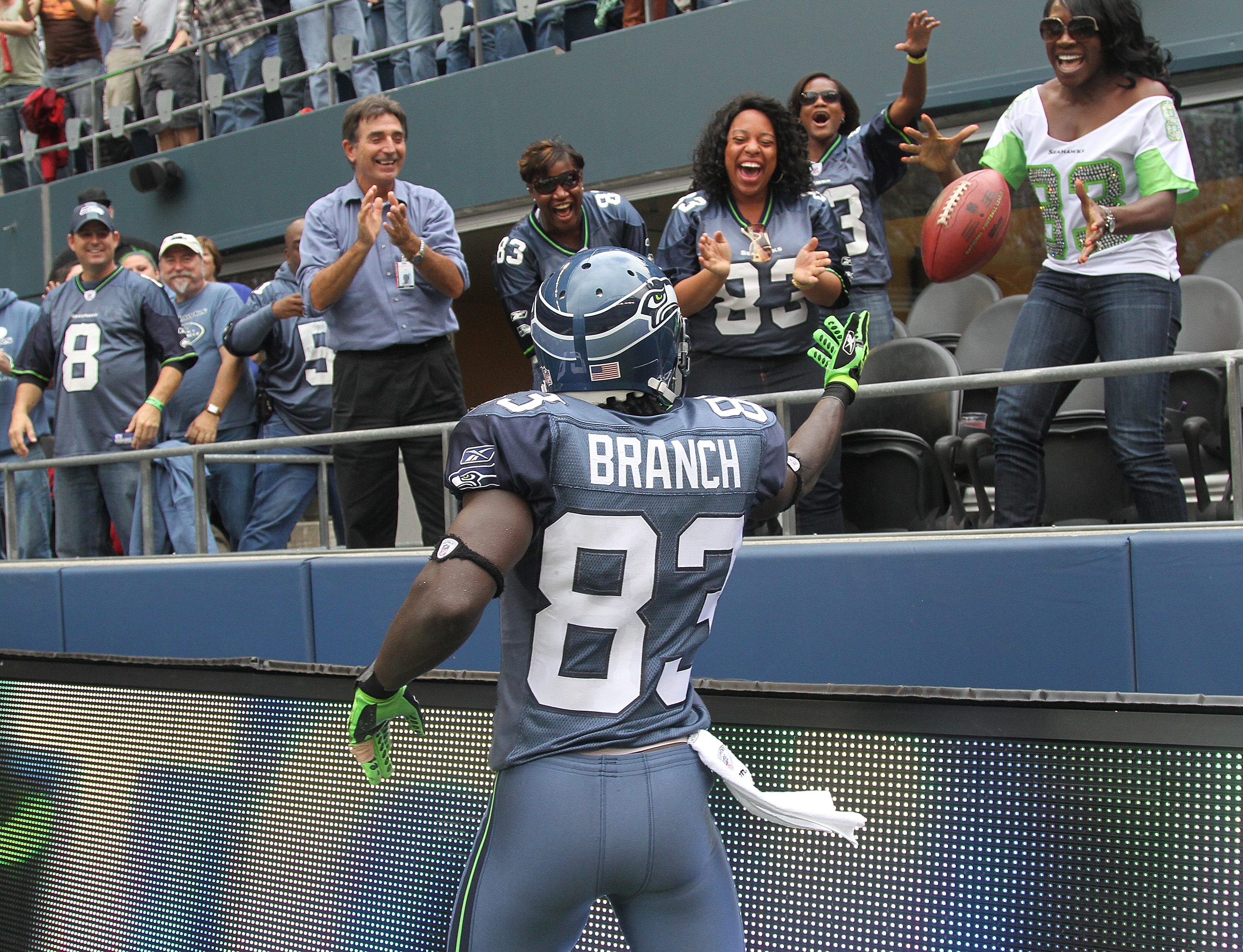 SEATTLE - SEPTEMBER 26:  Wide receiver Deion Branch #83 of the Seattle Seahawks tosses the ball to fans after scoring a touchdown against the San Diego Chargers at Qwest Field on September 26, 2010 in Seattle, Washington. The Seahawks defeated the Charger