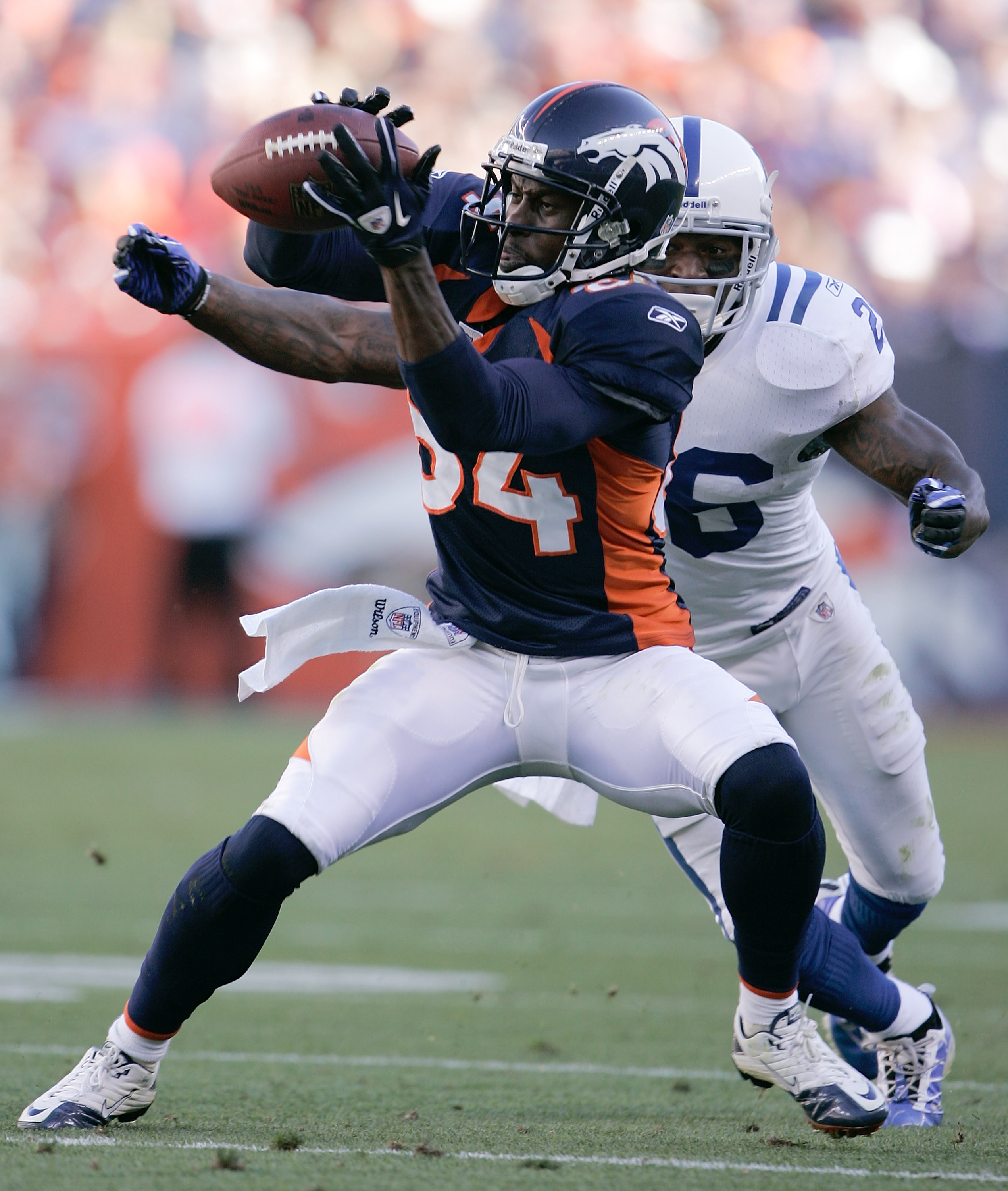 DENVER - SEPTEMBER 26:  Wide receiver Brandon Lloyd #84 of the Denver Broncos makes a catch in front of cornerback Kelvin Hayden #26 of the Indianapolis Colts during NFL action at INVESCO Field at Mile High on September 26, 2010 in Denver, Colorado. The C