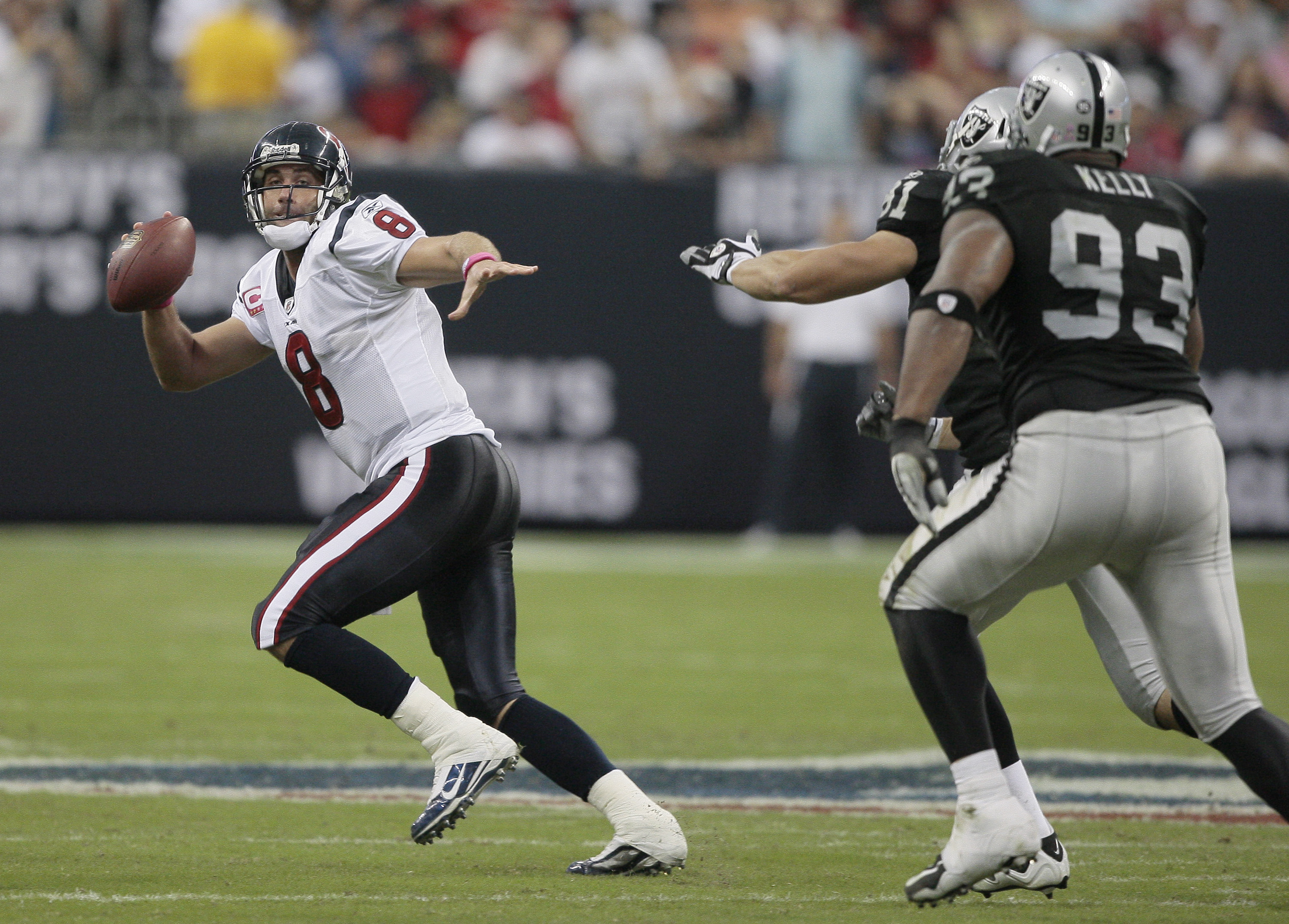 HOUSTON - OCTOBER 04:  Quarterback Matt Schaub #8 of the Houston Texans avoids pressure from defenive tackle Tommy Kelly #93 and Gerard Warren #61 of the Oakland Raiders at Reliant Stadium on October 4, 2009 in Houston, Texas.  (Photo by Bob Levey/Getty I