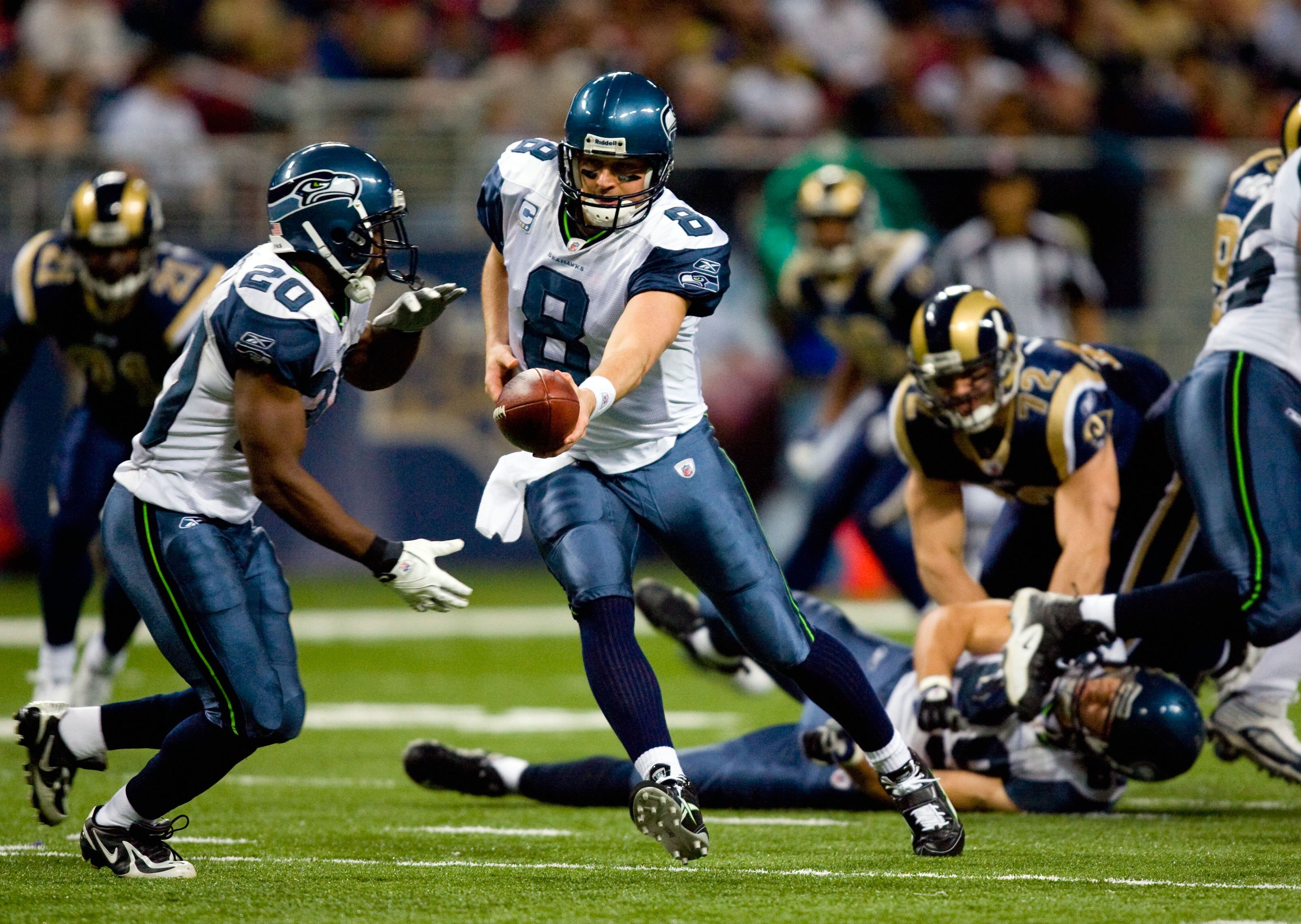 ST. LOUIS - NOVEMBER 29:  Quarterback Matt Hasselbeck #8 of the Seattle Seahawks looks to hand off the ball to Justin Forsett #20 during their NFL game against the St. Louis Rams at Edward Jones Dome on November 29, 2009 in St. Louis, Missouri. The Seahaw