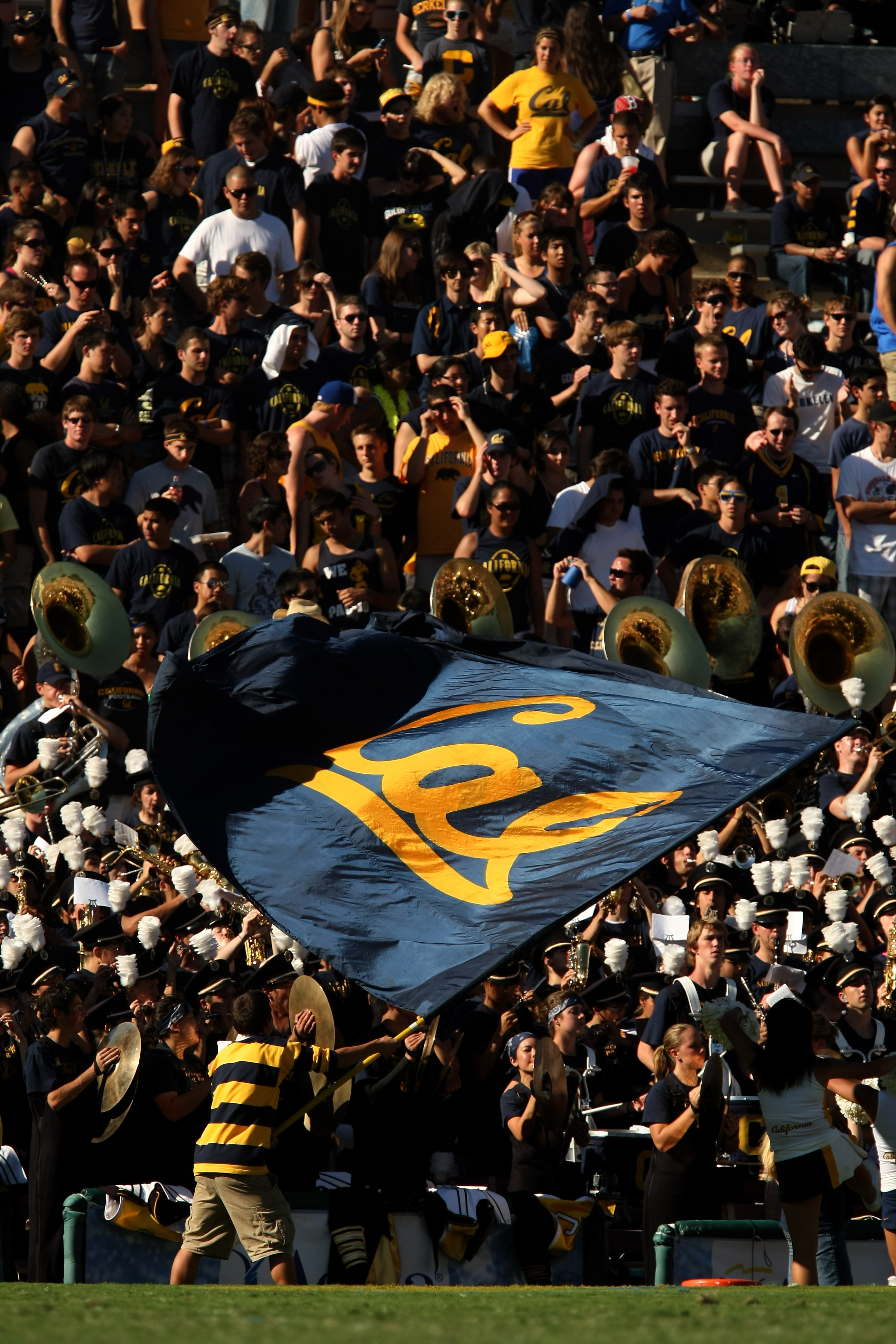 PASADENA, CA - OCTOBER 17:  A California Golden Bears cheerleader waves a flag in front of the Cal band and visitor's section in the game with the UCLA Bruins on October 17, 2009 at the Rose Bowl in Pasadena, California.   Cal won 45-26.  (Photo by Stephe