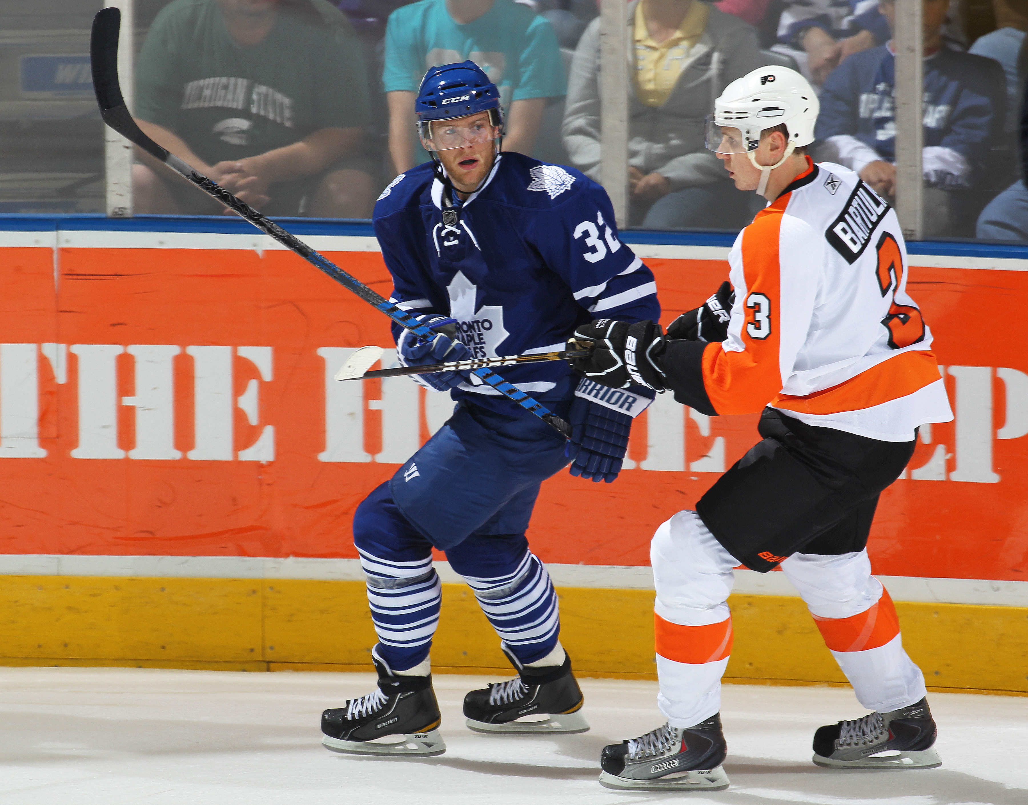 LONDON,ON - SEPTEMBER 23: Kris Versteeg #32 of the Toronto Maple Leafs is held in check by Oskars Bartulis #3 of the Philadelphia Flyers in a pre-season game on September 23,2010 at the John Labatt Centre in London, Ontario. The Leafs defeated the Flyers
