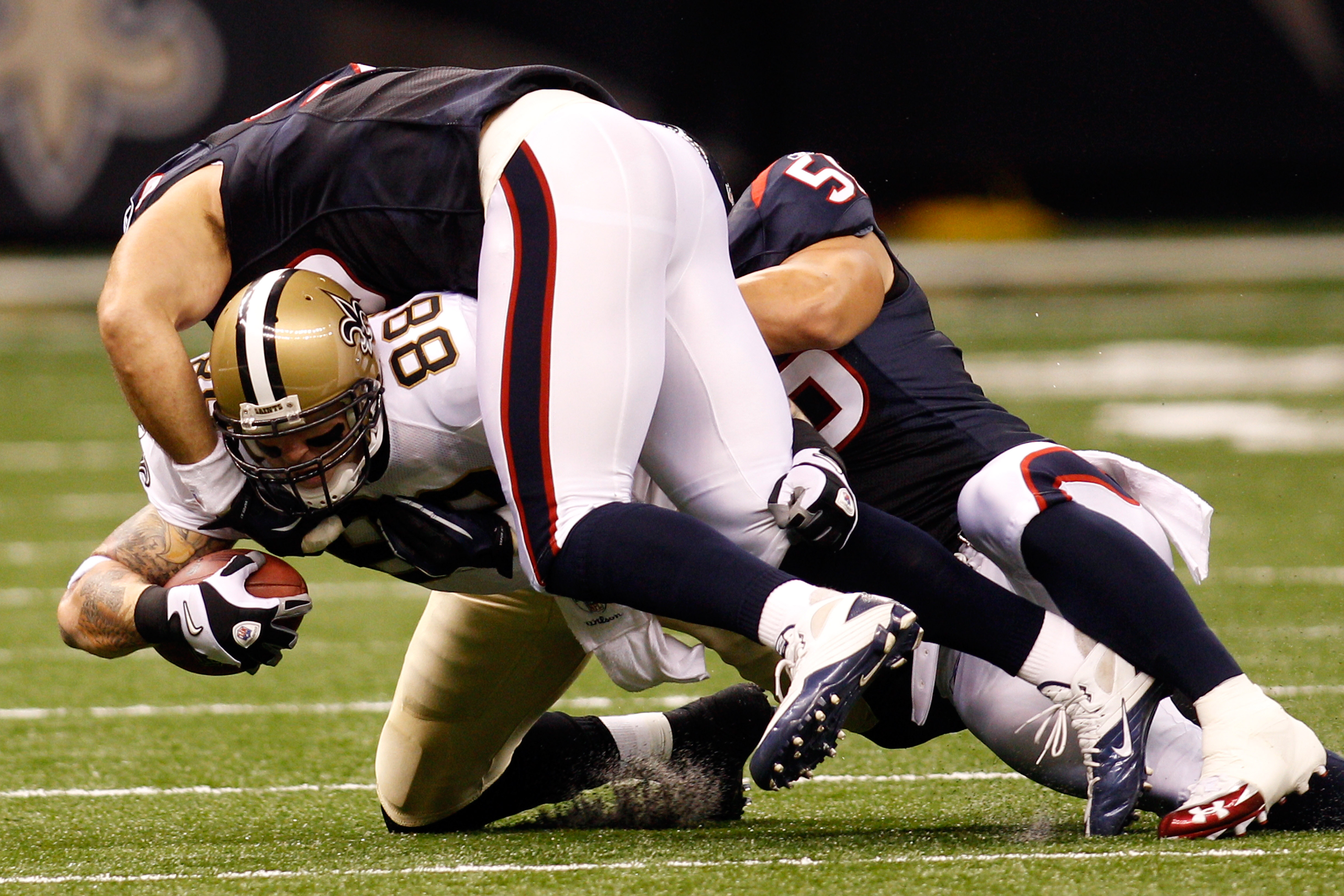 NEW ORLEANS - AUGUST 21:  Jeremy Shockey #88 of the New Orleans Saints is tackled by Connor Barwin #98 and Brian Cushing # 56 of the Houston Texans at the Louisiana Superdome on August 21, 2010 in New Orleans, Louisiana.  (Photo by Chris Graythen/Getty Im