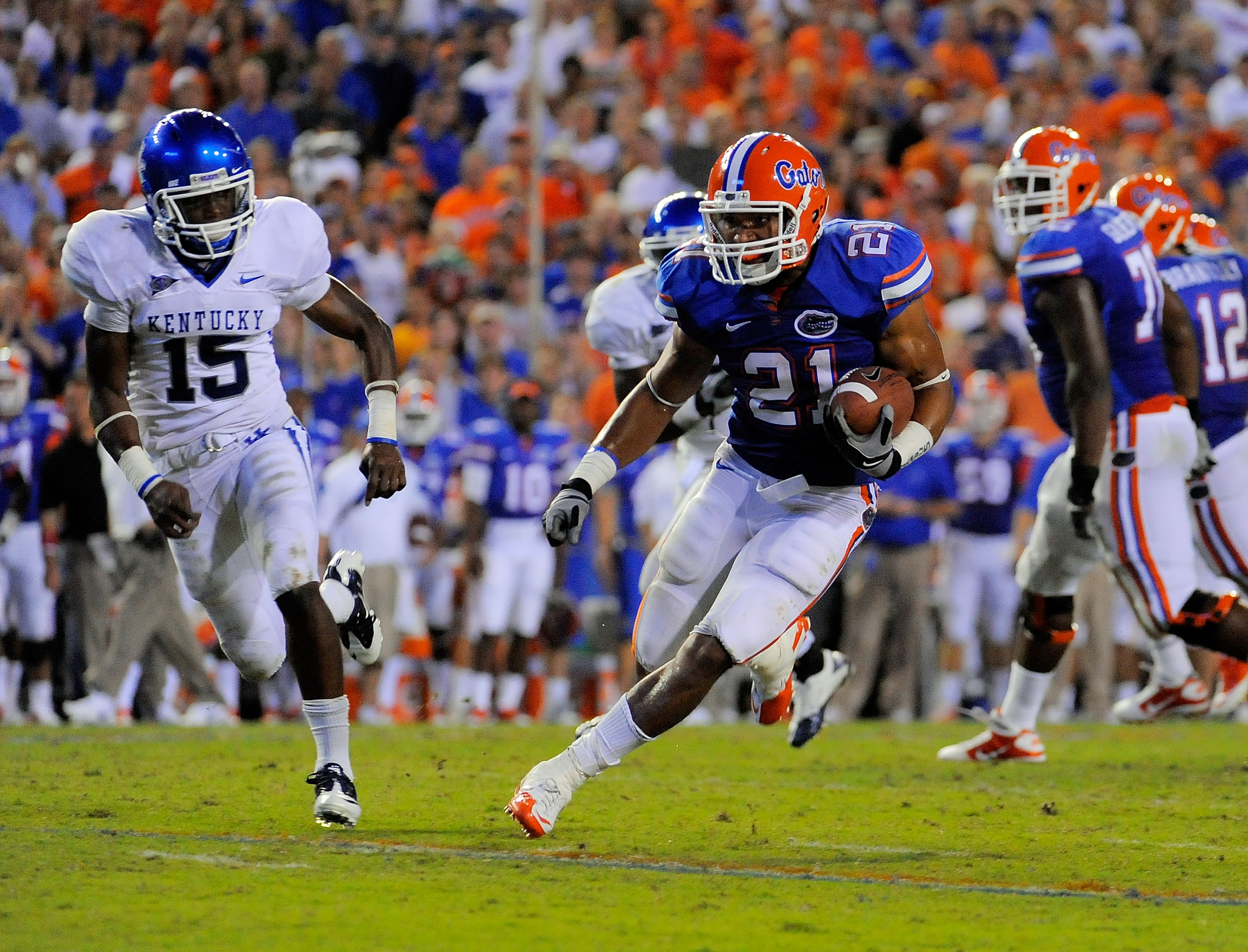 GAINESVILLE, FL - SEPTEMBER 25:  Running back Emmanuel Moody #21 of the Florida Gators gets past cornerback Martavius Neloms #15 of the Kentucky Wildcats at Ben Hill Griffin Stadium on September 25, 2010 in Gainesville, Florida. Florida defeated Kentucky