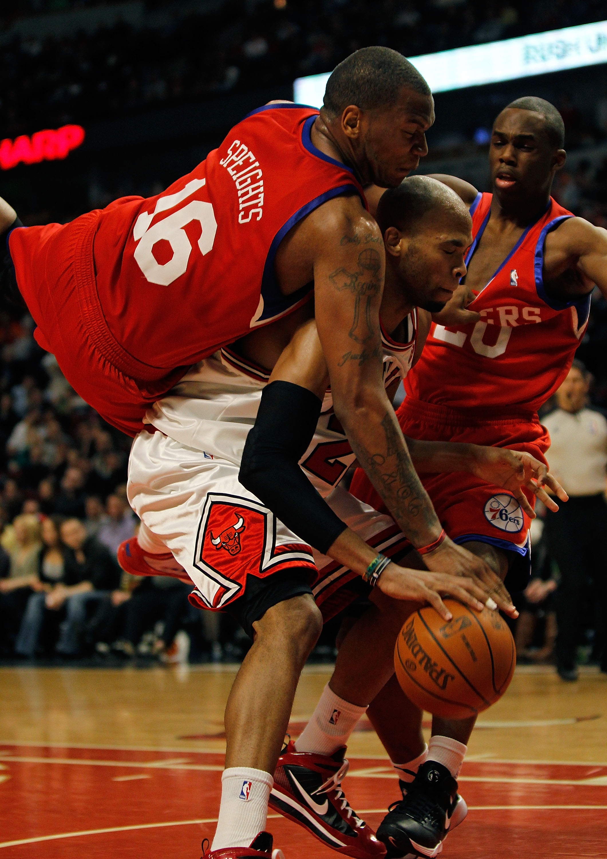 CHICAGO - FEBRUARY 20: Marreese Speights #16 of the Philadelphia 76ers falls over Taj Gibson #22 of the Chicago Bulls while holding the jersey of teammate Jodie Meeks #20 at the United Center on February 20, 2010 in Chicago, Illinois. The Bulls defeated t