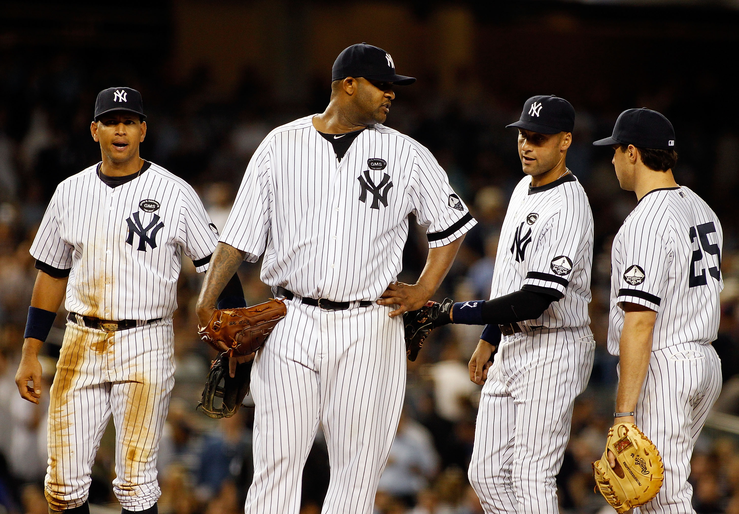 NEW YORK - SEPTEMBER 23:  CC Sabathia #52, Derek Jeter #2, Mark Teixeira #25 and Alex Rodriquez #13 of the New York Yankees looks on against the Tampa Bay Rays on September 23, 2010 at Yankee Stadium in the Bronx borough of New York City.  (Photo by Mike