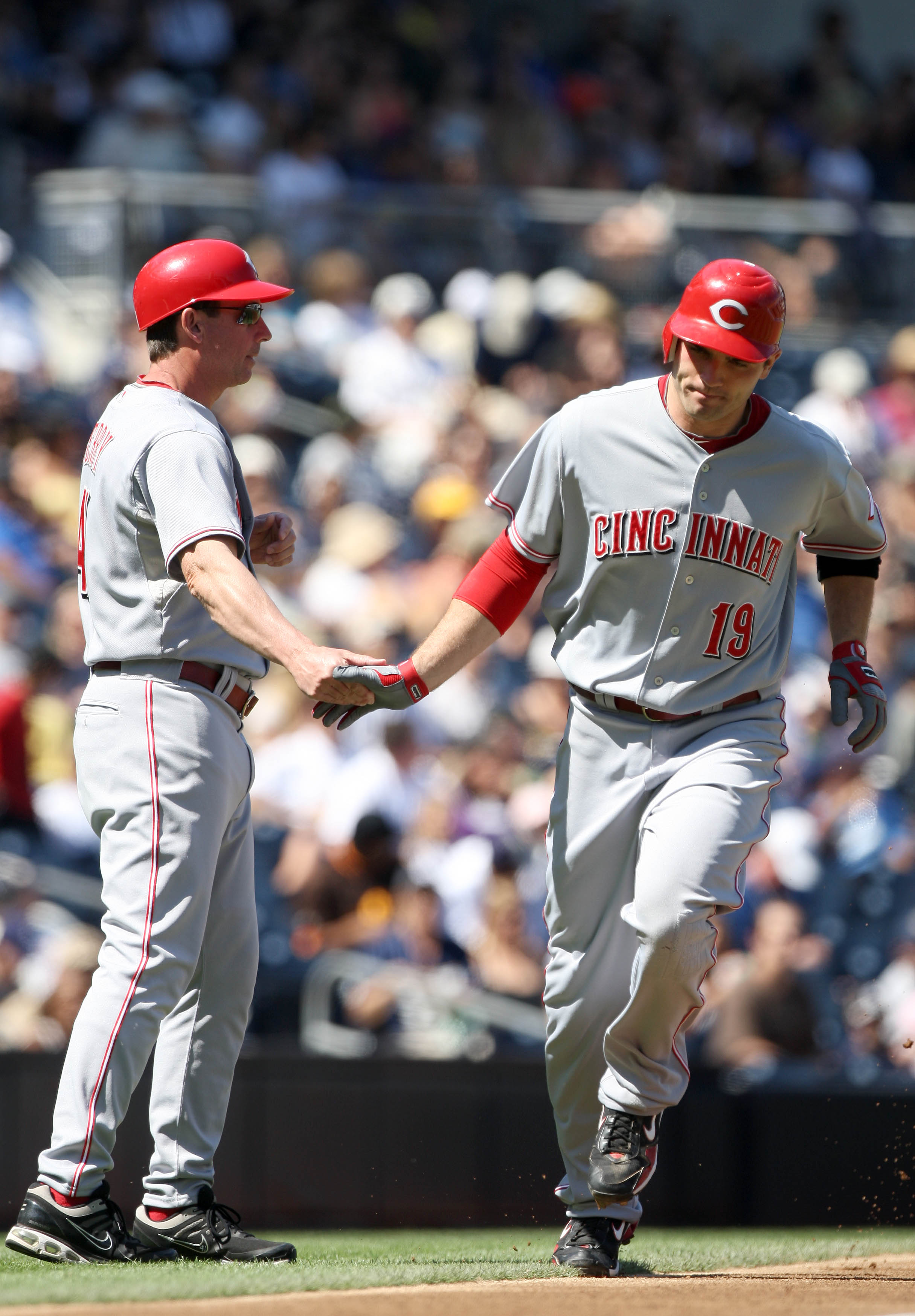 SAN DIEGO, CA - SEPTEMBER 26:  Joey Votto #19 of Cincinnati Reds is greeted by third base coach Mark Berry as he rounds the base after hitting a solo home run against the San Diego Padres during the first inning of their MLB game on September 26, 2010 at