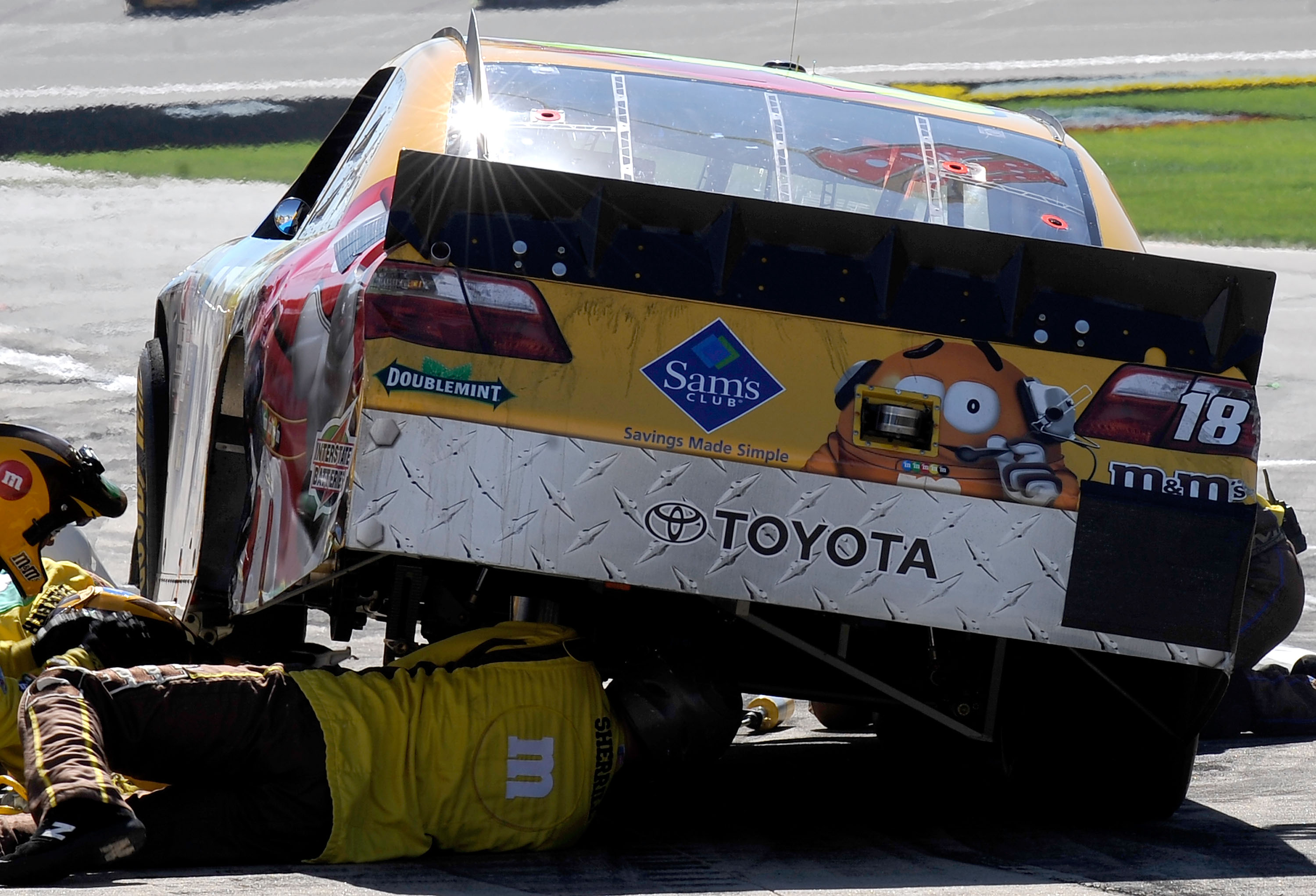 KANSAS CITY, KS - OCTOBER 03:  Crew members work on the car of Kyle Busch, driver of the #18 M&M's Toyota, during the NASCAR Sprint Cup Series Price Chopper 400 on October 3, 2010 in Kansas City, Kansas.  (Photo by Rusty Jarrett/Getty Images for NASCAR)