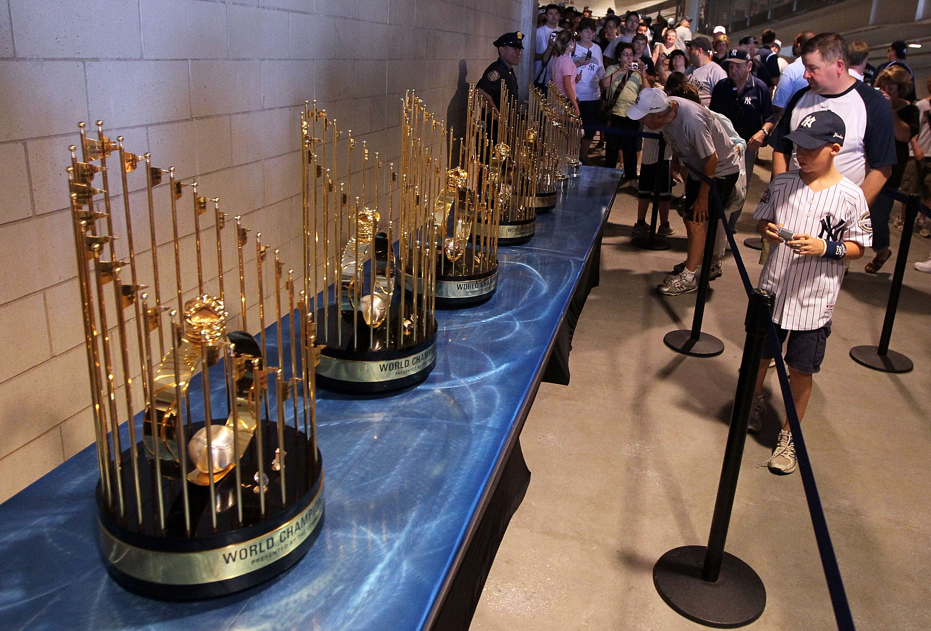 NEW YORK - JULY 04:  Fans photograph the seven World Series championship trophies won by the New York Yankees under the ownership of George Steinbrenner prior to the game against the Toronto Blue Jays on July 4, 2010 at Yankee Stadium in the Bronx borough