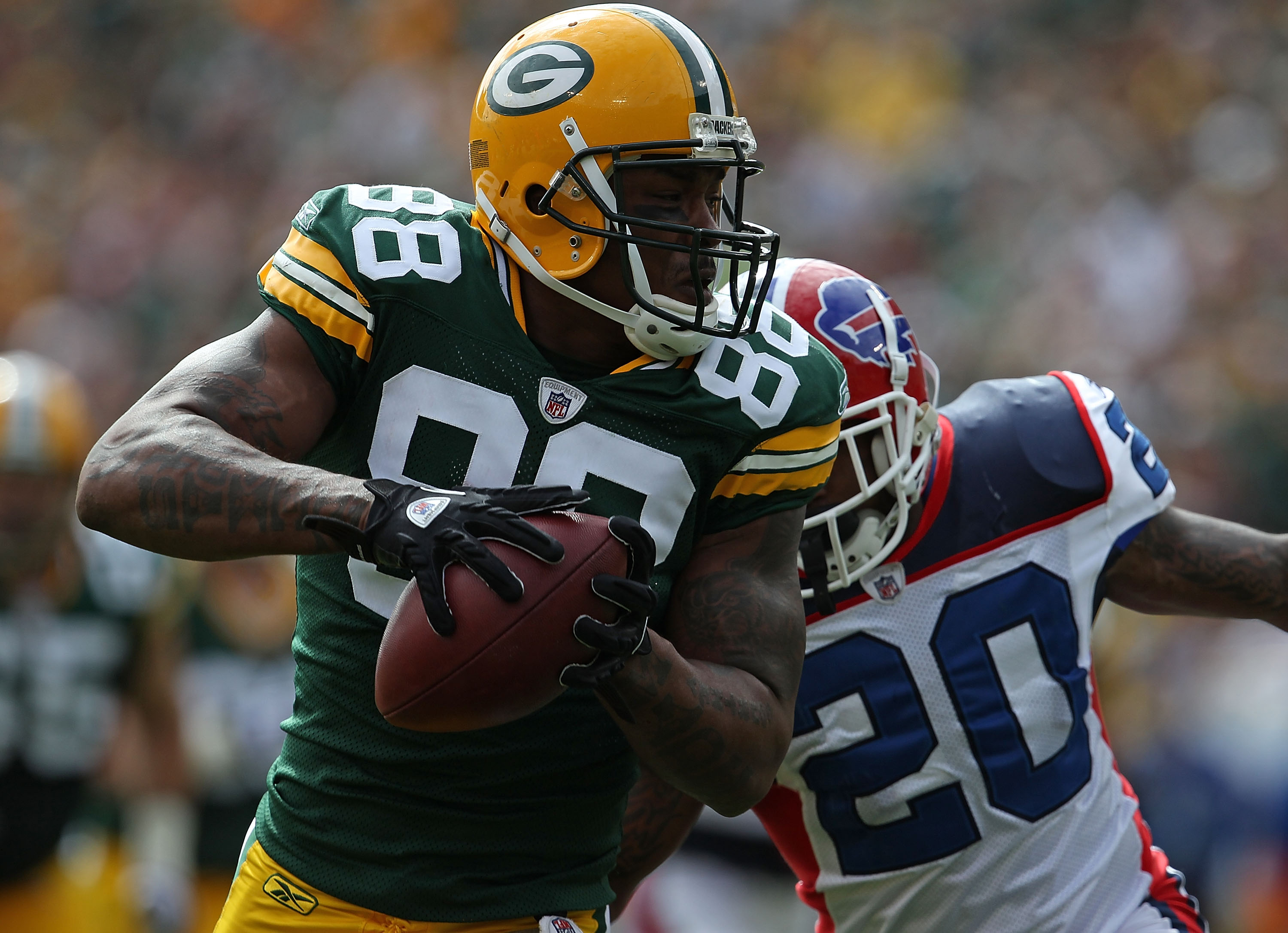 GREEN BAY, WI - SEPTEMBER 19: Jermichael Finley #88 of the Green Bay Packers grabs a pass in front of Donte Whitner #20 of the Buffalo Bills at Lambeau Field on September 19, 2010 in Green Bay, Wisconsin. The Packers defeated the Bills 34-7. (Photo by Jon