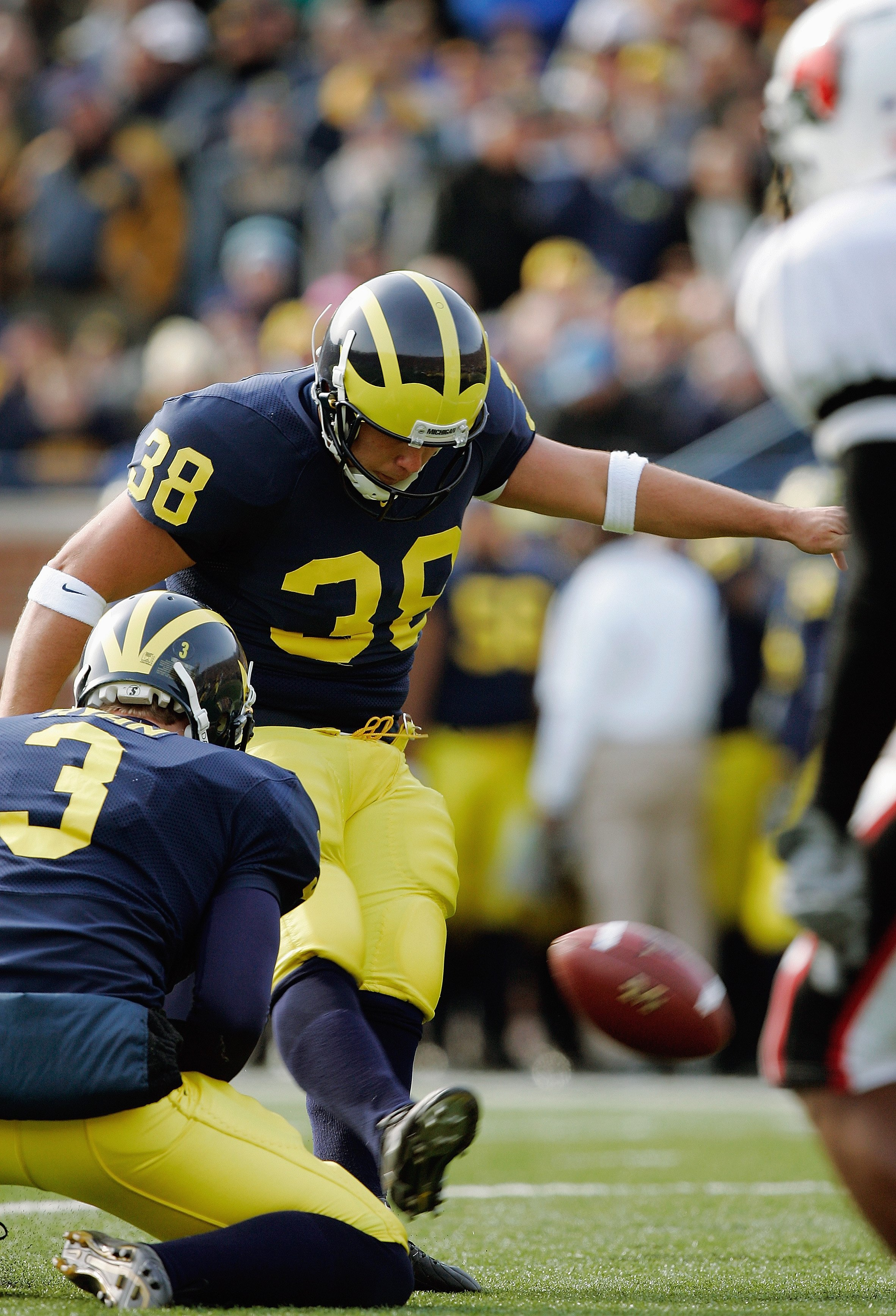 ANN ARBOR, MI - NOVEMBER 4:  Garrett Rivas #38 of the Michigan Wolverines kicks from holder Ross Ryan #3 during the NCAA game against the Ball State Cardinals on November 4, 2006 at Michigan Stadium in Ann Arbor, Michigan. Michigan won 34-26. (Photo by Br