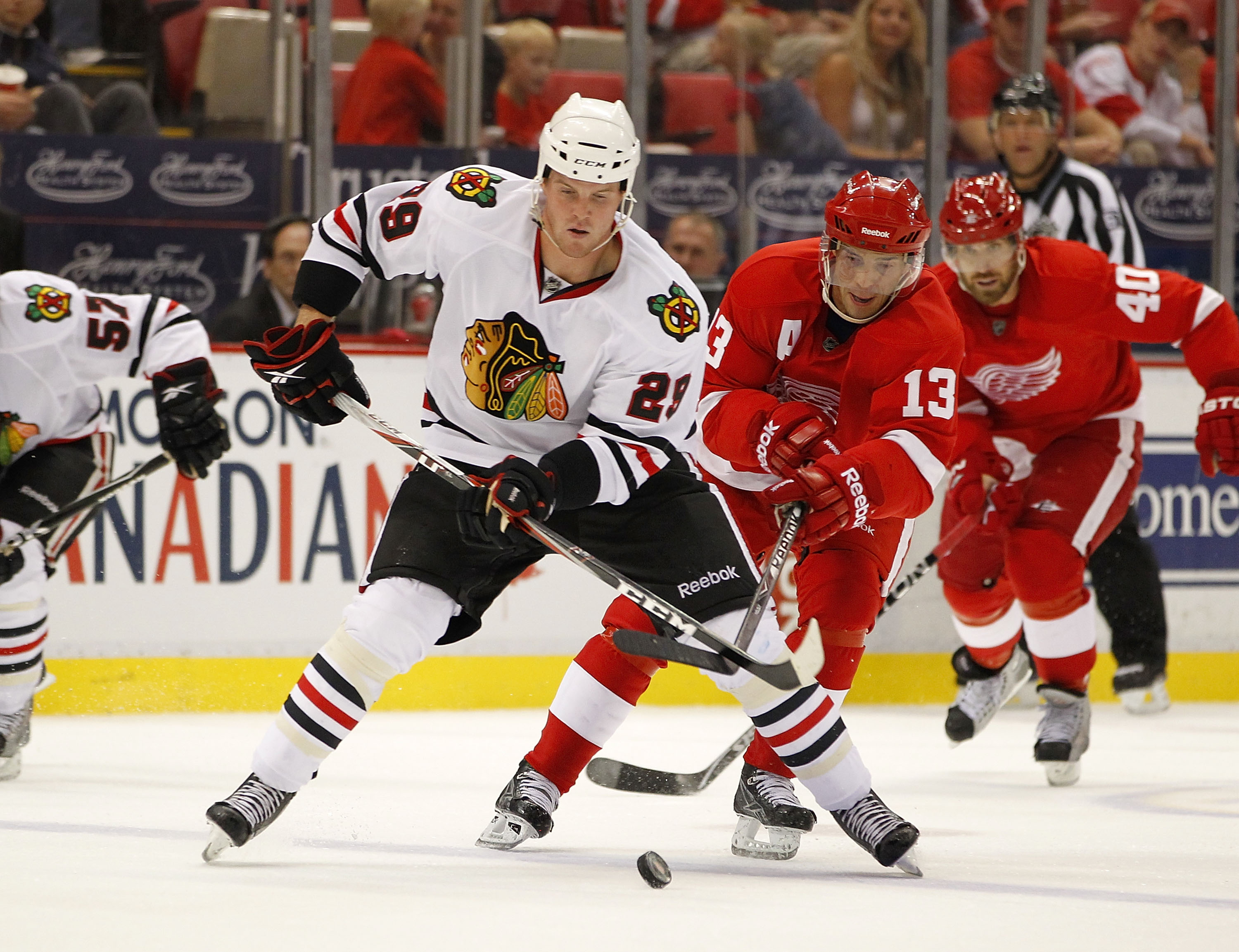 DETROIT - SEPTEMBER 24:  Bryan Bickell #29 of the Chicago Blackhawks tries to control the puck in front of Pavel Datsyuk #13 of the Detroit Red Wings during a pre season game on September 24, 2010 at Joe Louis Arena in Detroit, Michigan.  (Photo by Gregor