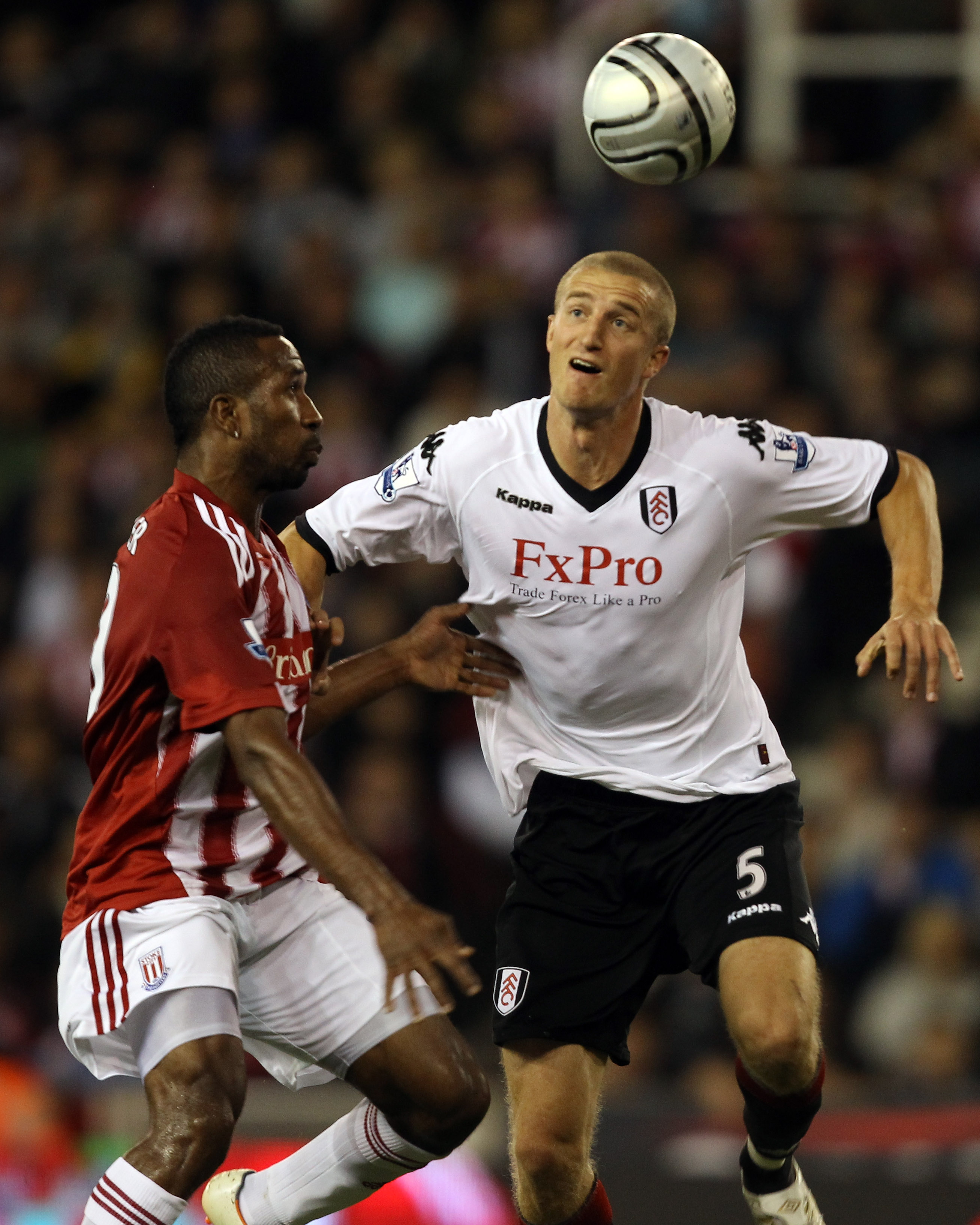 STOKE ON TRENT, ENGLAND - SEPTEMBER 21:  Ricardo Fuller of Stoke is challenged by Brede Hangeland of Fulham during the Carling Cup 3rd Round tie between Stoke City and Fulham at the Britannia Stadium on September 21, 2010 in Stoke on Trent, England.  (Pho