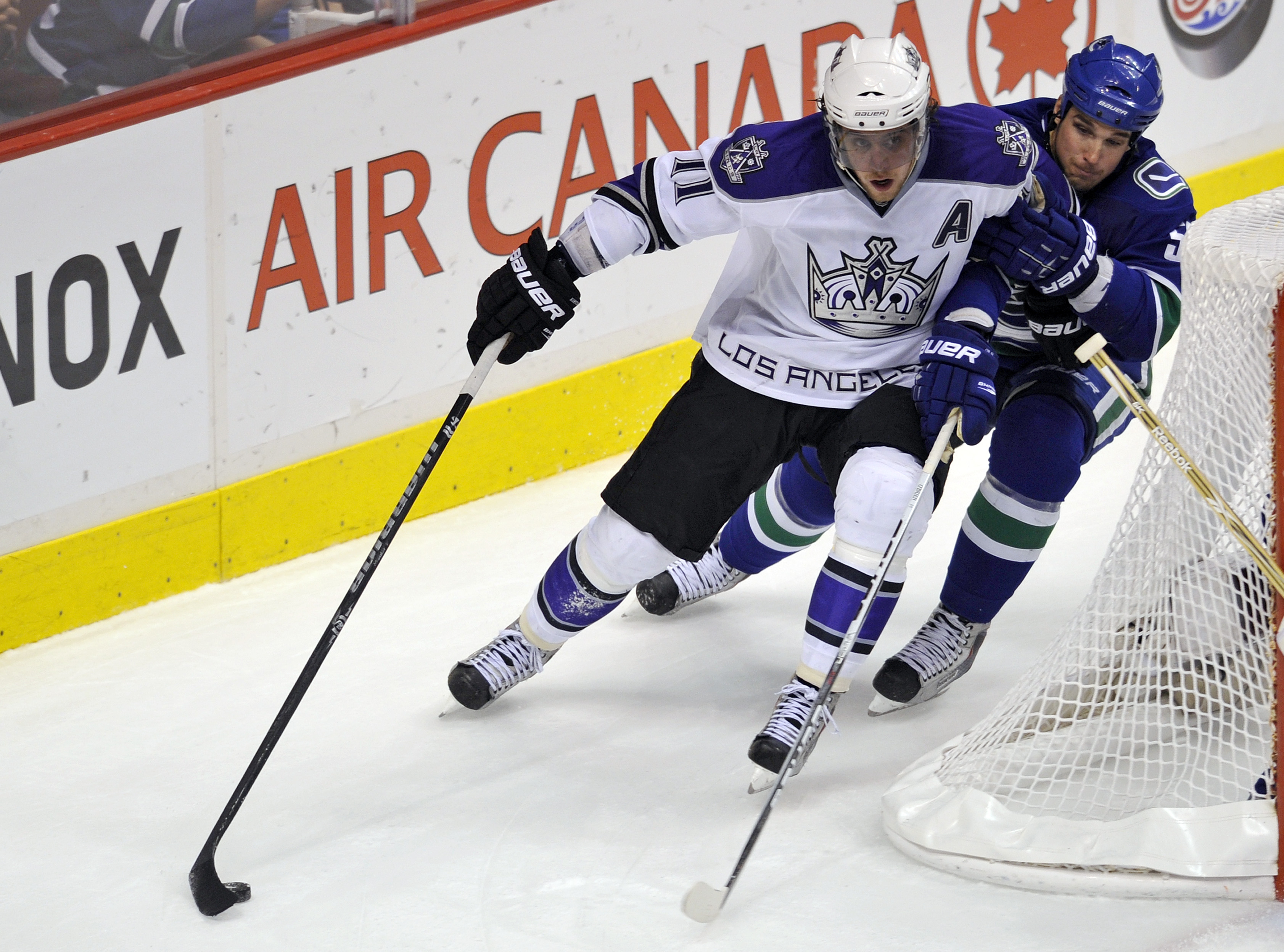 VANCOUVER, CANADA - APRIL 23:  Anze Kopitar #11 of the Los Angeles Kings tries for a wrap-around while being checked by Shane O'Brien #55 of the Vancouver Canucks during the second period in Game Five of the Western Conference Quarterfinals during the 201