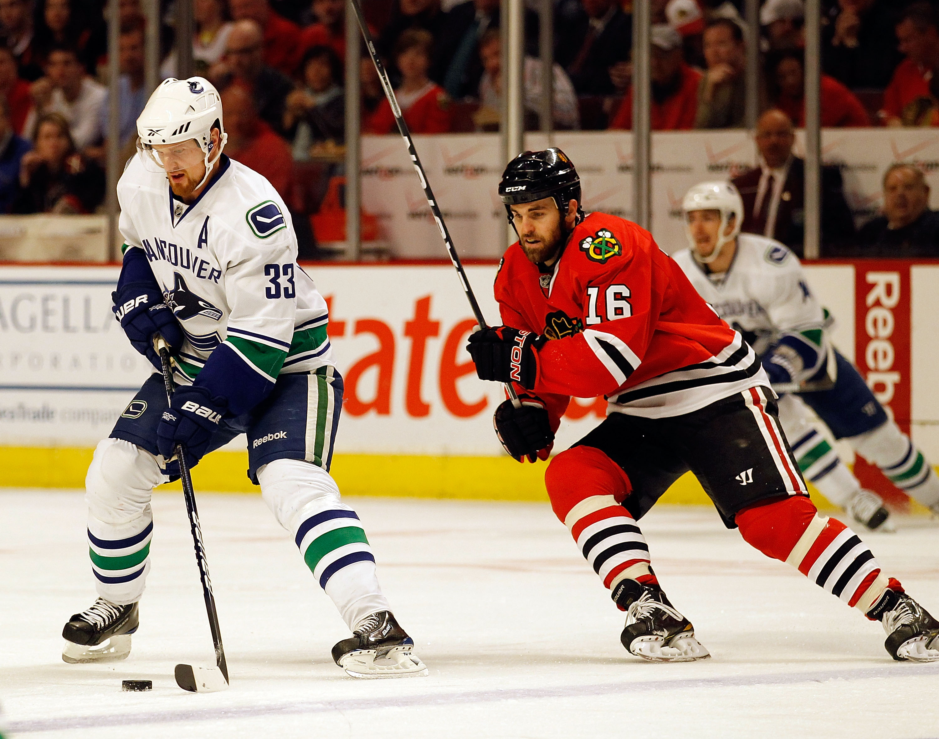 CHICAGO - MAY 09: Henrik Sedin #33 of the Vancouver Canucks moves across the ice with the puck as Andrew Ladd #16 of the Chicago Blackhawks closes in in Game Five of the Western Conference Semifinals during the 2010 NHL Stanley Cup Playoffs at United Cent