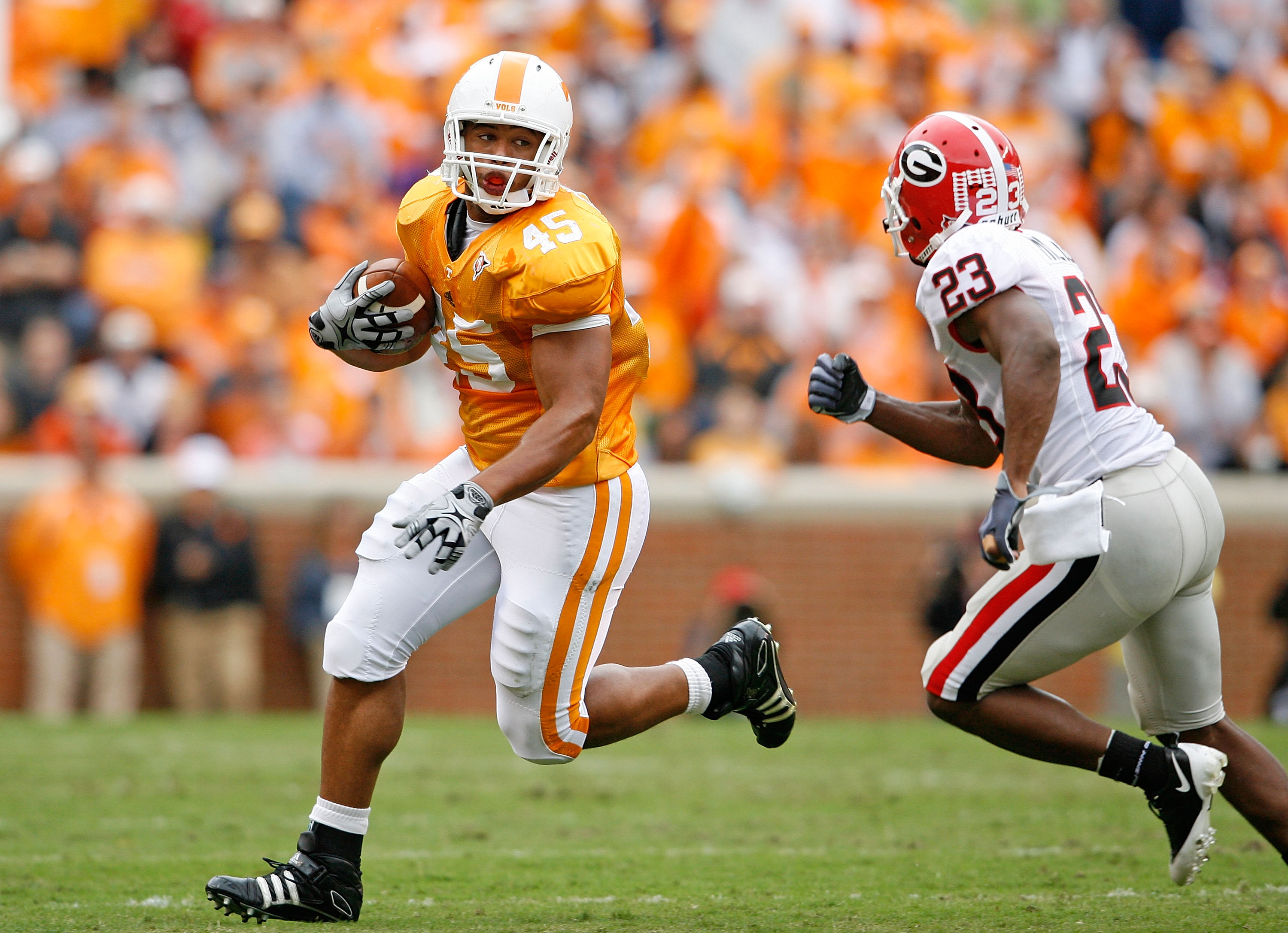 KNOXVILLE, TN - OCTOBER 10: Kevin Cooper #45 of the Tennessee Volunteers runs with the ball while defended by Prince Miller #23 of the Georgia Bulldogs during the SEC game at Neyland Stadium on October 10, 2009 in Knoxville, Tennessee. (Photo by Andy Lyon