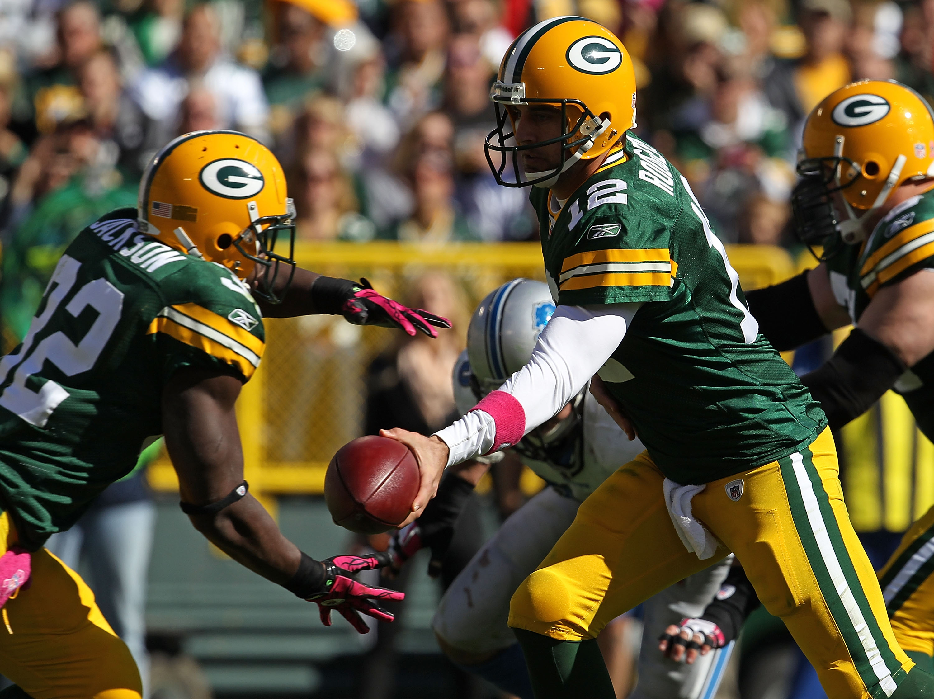 GREEN BAY, WI - OCTOBER 03: Aaron Rodgers #12 of the Green Bay Packers hands off to Brandon Jackson #32 against the Detroit Lions at Lambeau Field on October 3, 2010 in Green Bay, Wisconsin. The Packers defeated the Lions 28-26. (Photo by Jonathan Daniel/