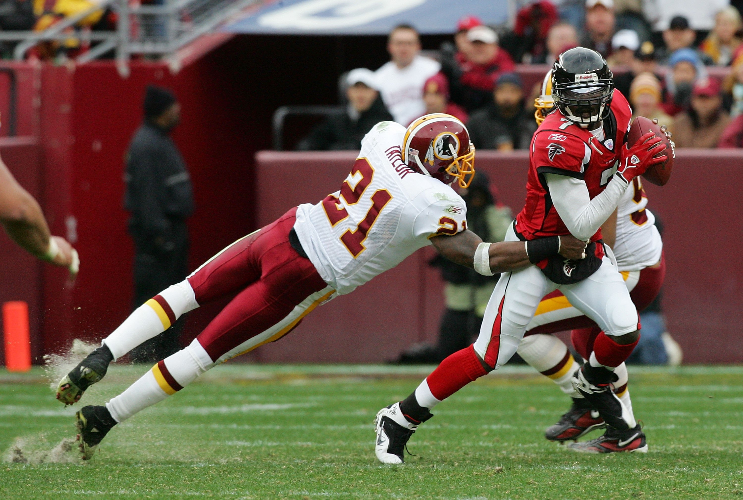 LANDOVER, MD - DECEMBER 03:   Michael Vick #7 of the Atlanta Falcons avoids a tackle from Sean Taylor #21 of the Washington Redskins December 3, 2006 at FedEx Field in Landover, Maryland.The Falcons defeated the Redskins, 24-14.  (Photo by Jim McIsaac/Get