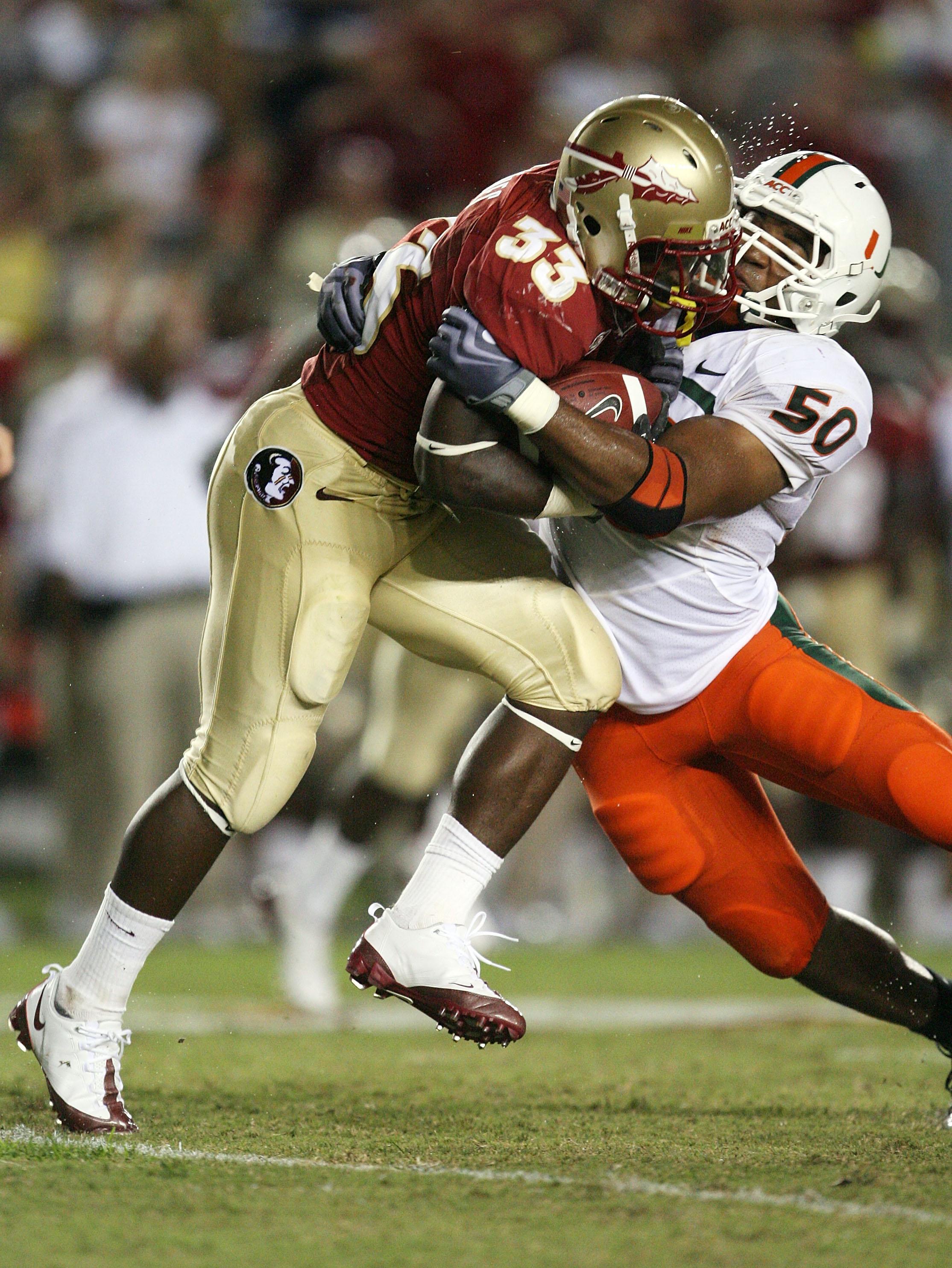 TALLAHASSEE, FL - SEPTEMBER 07:  Linebacker Darryl Sharpton #50 of the Miami Hurricanes brings down running back Ty Jones #33 of the Florida State Seminoles at Doak Campbell Stadium on September 7, 2009 in Tallahassee, Florida. Miami defeated Florida Stat