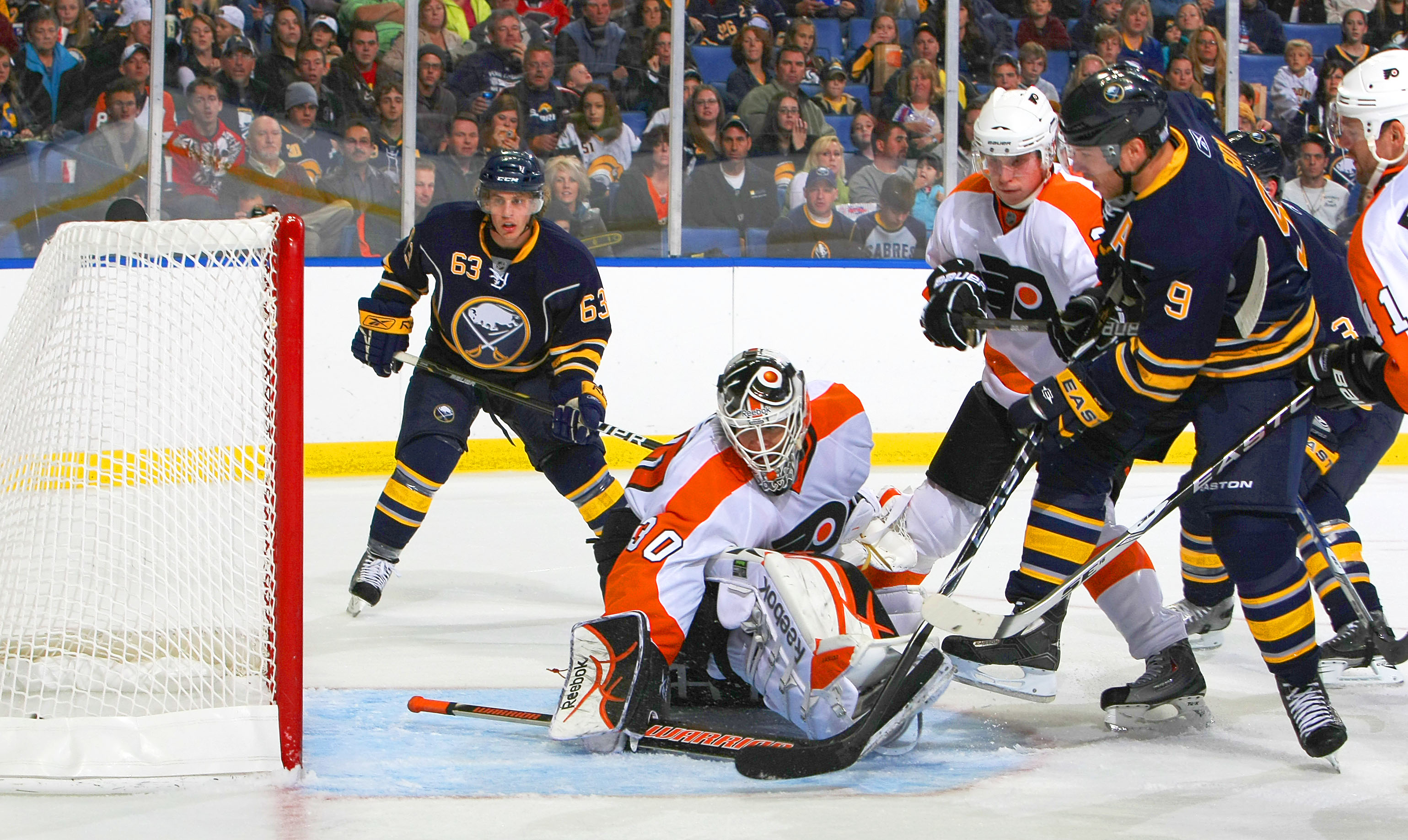 BUFFALO - OCTOBER 3:  Derek Roy #9 of the Buffalo Sabres scores a goal against Johan Backlund #30 of the Philadelphia Flyers as Tyler Ennis #63 of the Buffalo Sabres and Oskars Bartulis #3 of the Philadelphia Flyers both look on during their NHL game at H