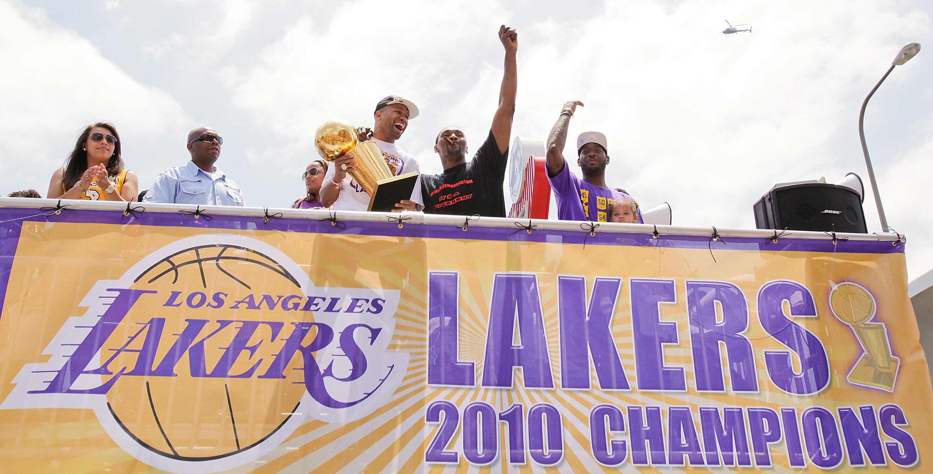 LOS ANGELES, CA - JUNE 21:  (3L-R) Los Angeles Lakers point guard Derek Fisher hoists the championship trophy with small forward Ron Artest (C) and power forward Josh Powell (R) while riding in the victory parade for the the NBA basketball champion team o