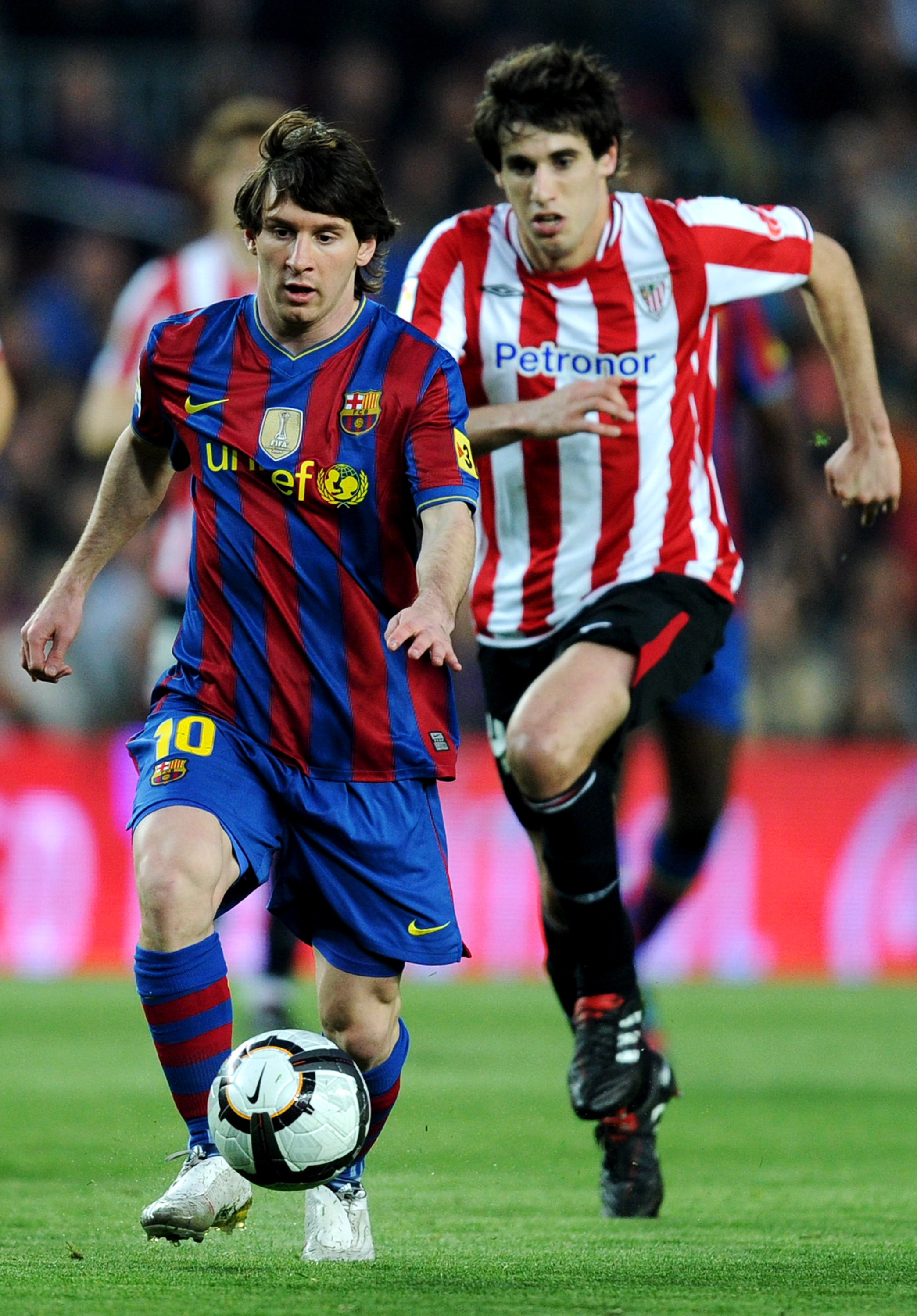 BARCELONA, SPAIN - APRIL 03:  Lionel Messi (L) of FC Barcelona runs for the ball pursued by Javi Martinez of Athletic Bilbao during the La Liga match between Barcelona and Athletic Bilbao at the Camp Nou Stadium on April 3, 2010 in Barcelona, Spain. Barce