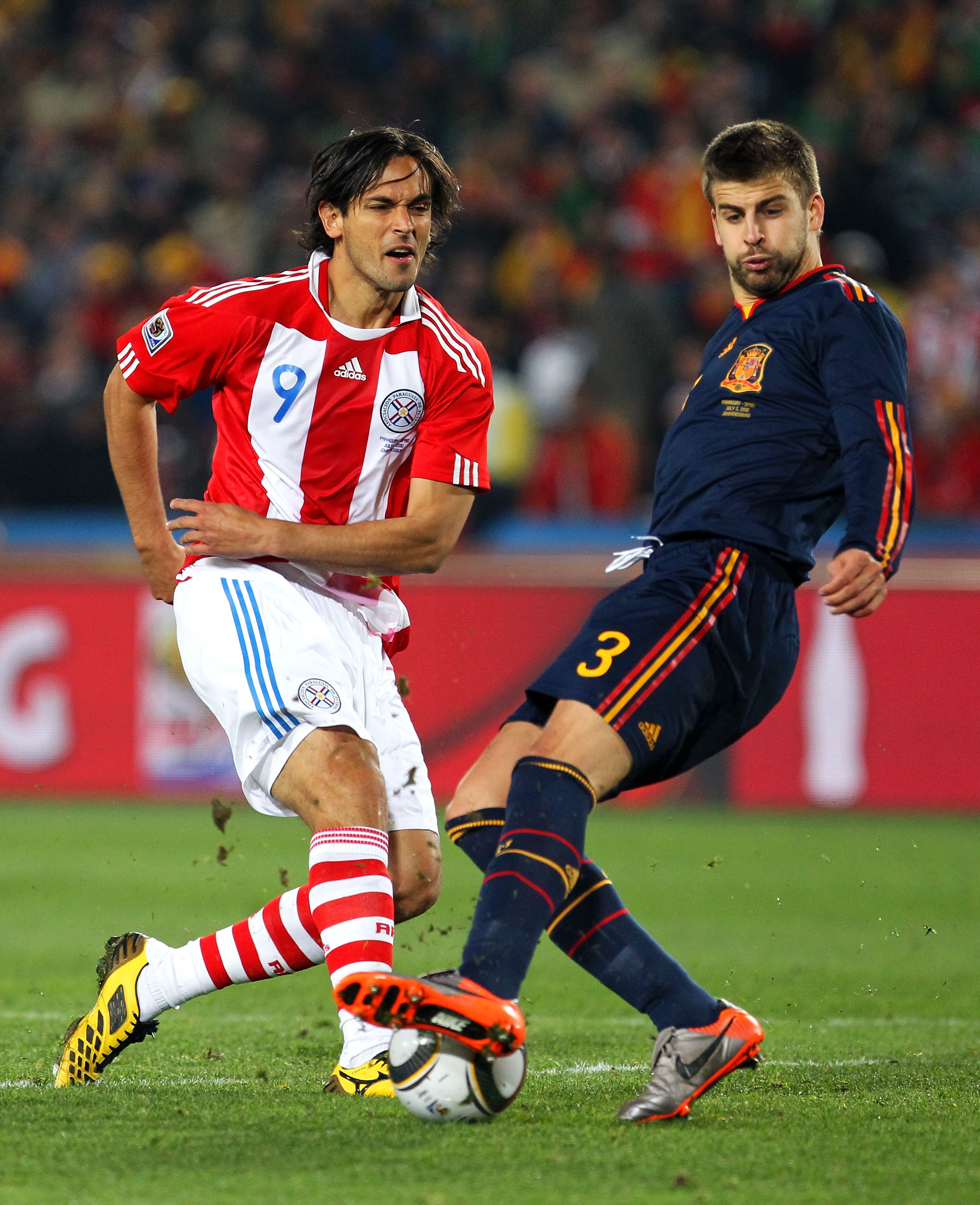 JOHANNESBURG, SOUTH AFRICA - JULY 03:  Gerard Pique of Spain tackles Roque Santa Cruz of Paraguay during the 2010 FIFA World Cup South Africa Quarter Final match between Paraguay and Spain at Ellis Park Stadium on July 3, 2010 in Johannesburg, South Afric