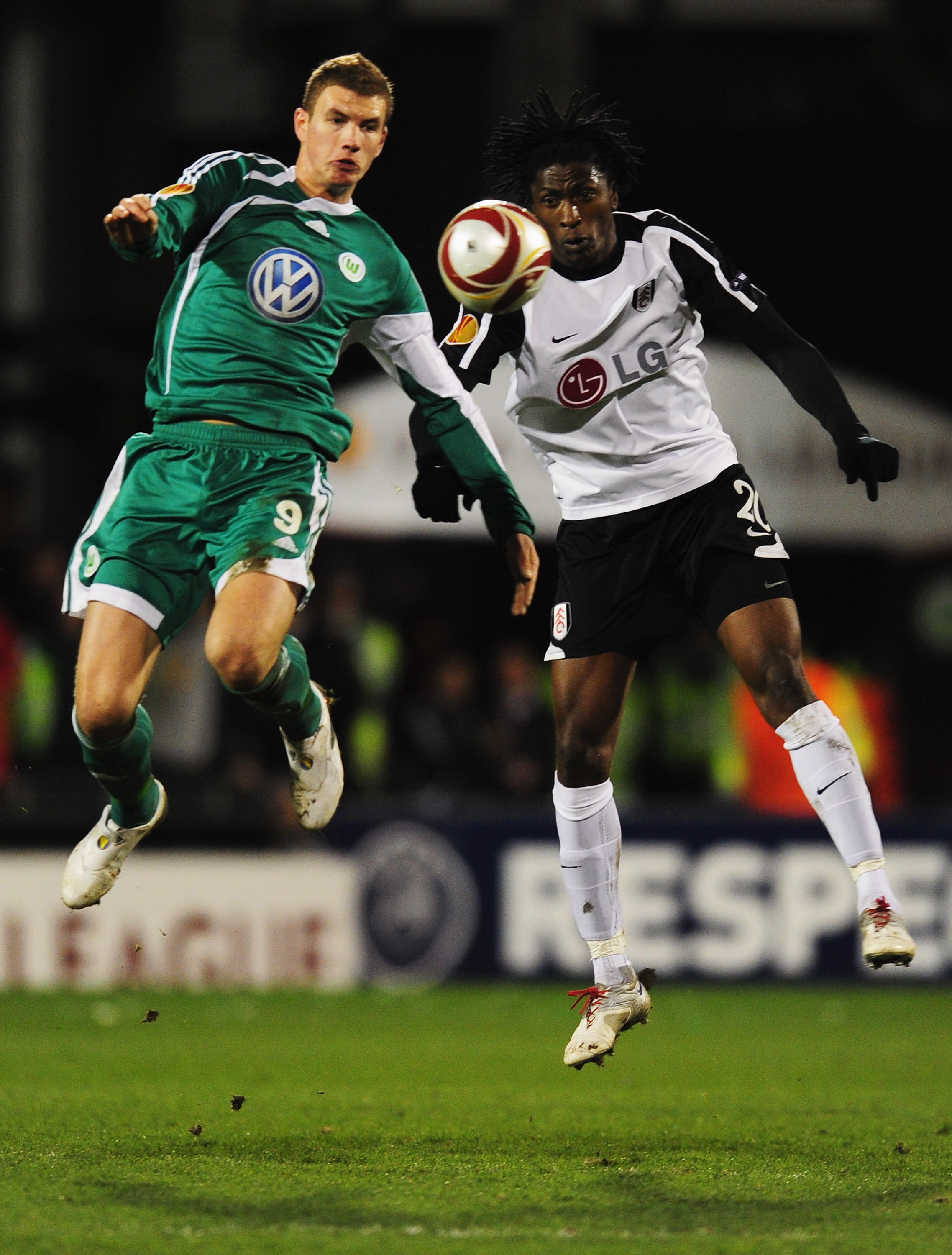 LONDON, ENGLAND - APRIL 01:  Dickson Etuhu of Fulham jumps with Edin Dzeko of VfL Wolfsburg (R) during the UEFA Europa League quarter final first leg match between Fulham and Vfl Wolfsburg at Craven Cottage on April 1, 2010 in London, England.  (Photo by