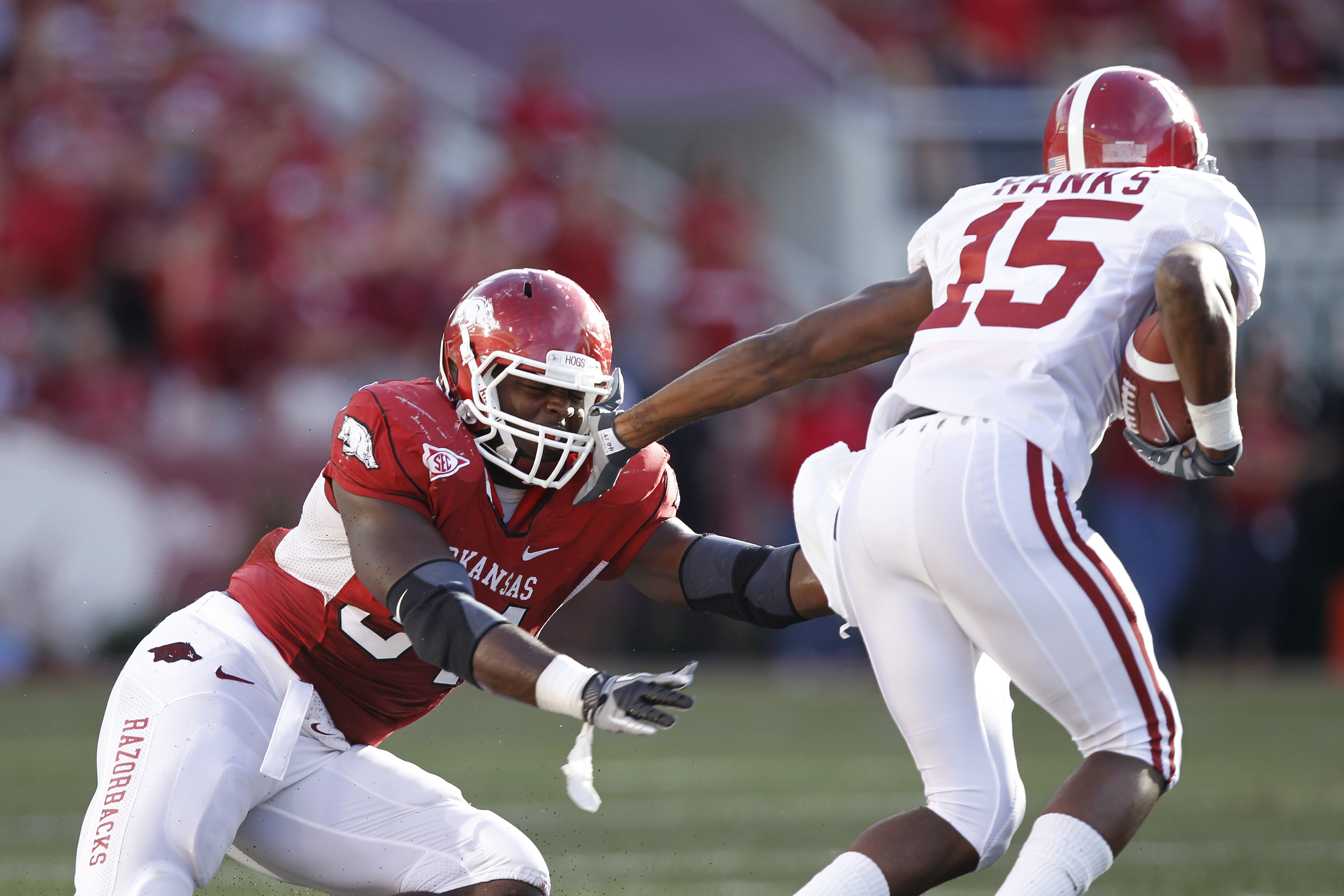 FAYETTEVILLE - SEPTEMBER 25: Darius Hanks #15 of the Alabama Crimson Tide tries to get around a tackle attempt by Jerry Franklin #34 of the Arkansas Razorbacks at Donald W. Reynolds Razorback Stadium on September 25, 2010 in Fayetteville, Arkansas. Alabam