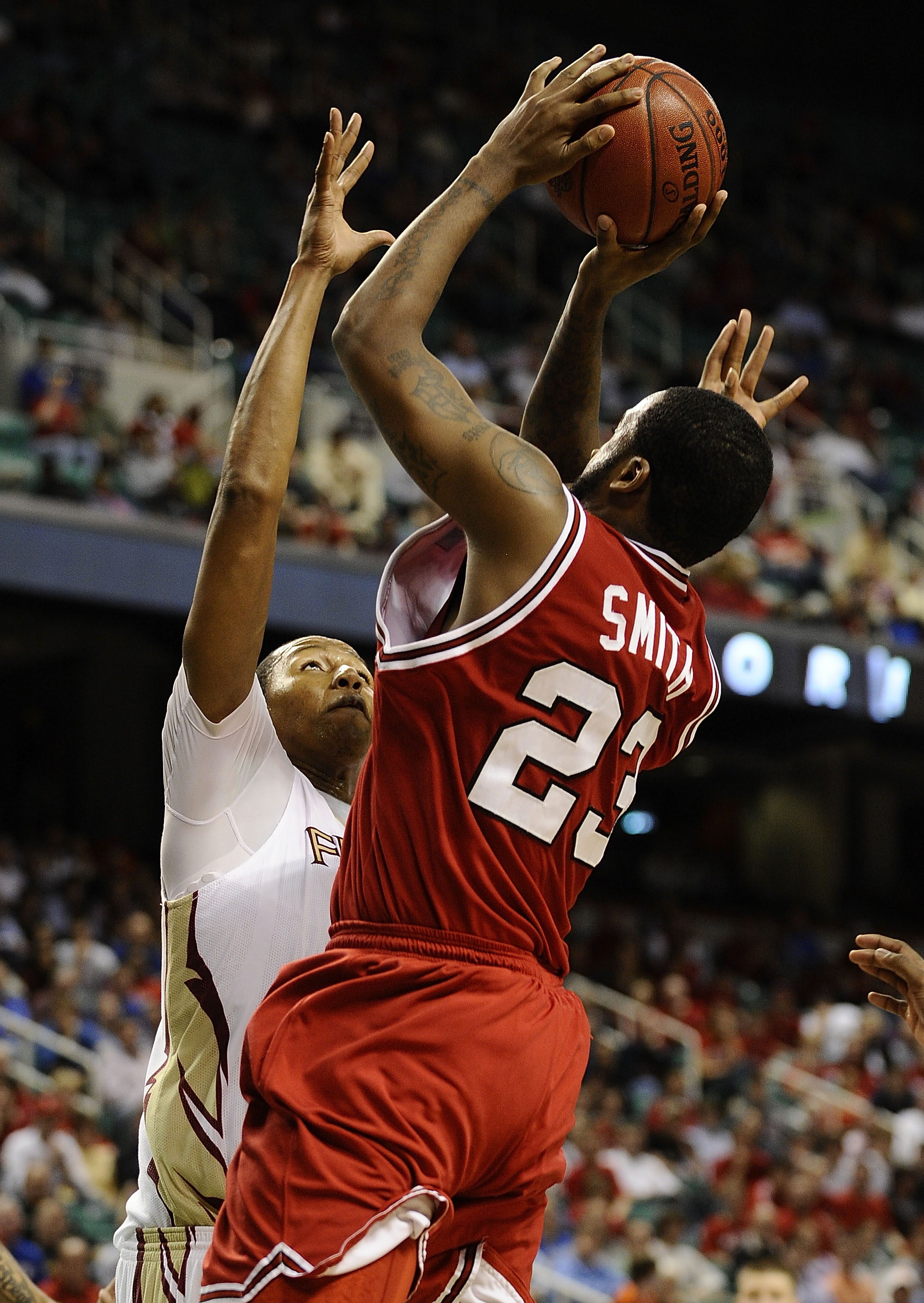 GREENSBORO, NC - MARCH 12:  Tracy Smith #23 of the North Carolina State Wolfpack shoots over Xavier Gibson #1 Florida State Seminoles in their quarterfinal game in the 2010 ACC Men's Basketball Tournament at the Greensboro Coliseum on March 12, 2010 in Gr